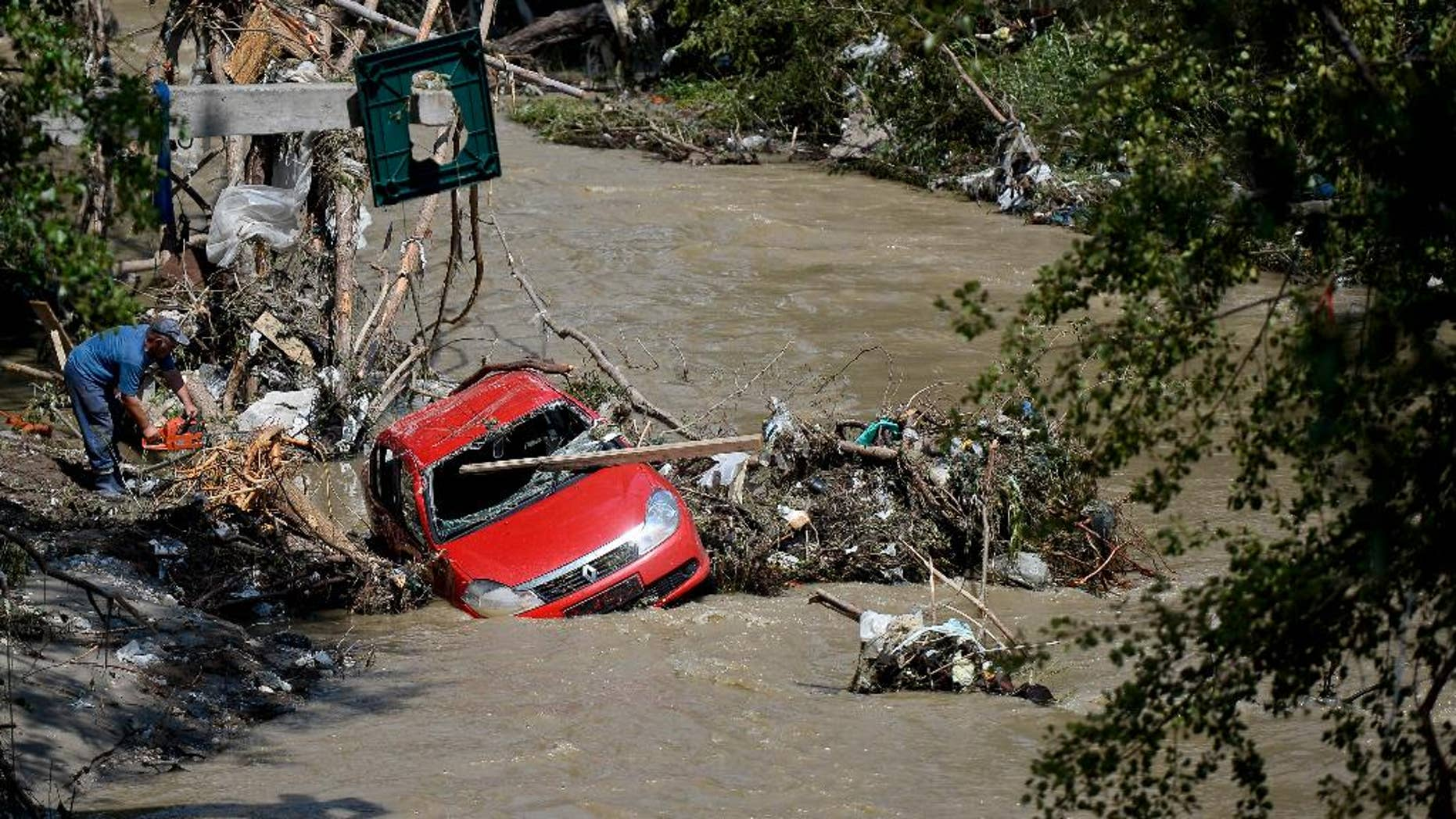 A man uses a chainsaw to cut tree stumps to free a washed up car carried downstream by the recent flash flood, in Bascov city, Arges, Romania, Wednesday, July 30, 2014. Over a thousand people were evacuated and 99 homes were destroyed as floods raged in the south eastern part of Romania. (AP Photo/Octav Ganea, Mediafax) ROMANIA OUT