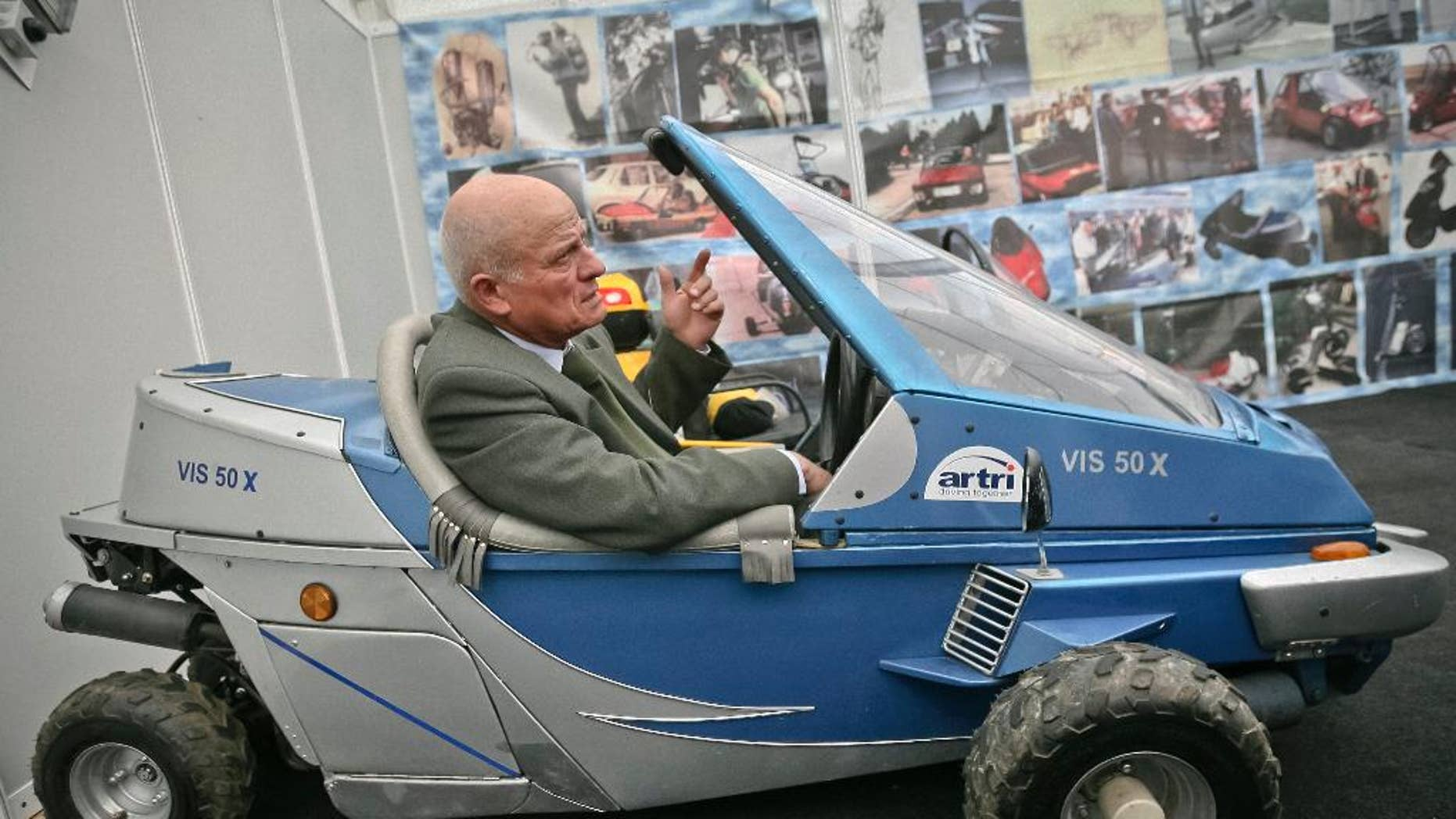 """In a photo taken on March 24, 2009, Justin Capra, a Romanian inventor who claimed he beat the Americans to make the world's first jet-pack, seen on photo wall behind top left,  gestures sitting in a fuel efficient vehicle he designed at an inventions fair in Cluj, Romania. Capra, who in 1956 invented the """"flying rucksack,"""" a personal flying machine, very similar, according to him to the one built in 1962 in the U.S. by Bell Aircraft Corp., has died Monday, Jan. 19, 2015, aged 81.(AP Photo/Mircea Rosca)"""