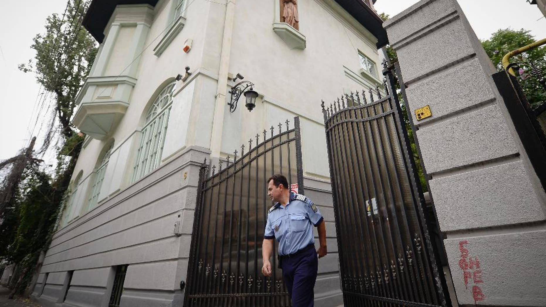 A police officer exits the gate of Romanian Prince Paul's house, in Bucharest, Romania, Thursday, Sept. 10, 2015. The prince's lawyer says his client, who is a grandson to Romania's King Carol II and a nephew to former King Michael, will pay 4.7 million pounds ($7.28 million) to a British Royalty Magazine editor, Marco Houston, following a court decision. (Octav Ganea, Mediafax via AP) ROMANIA OUT
