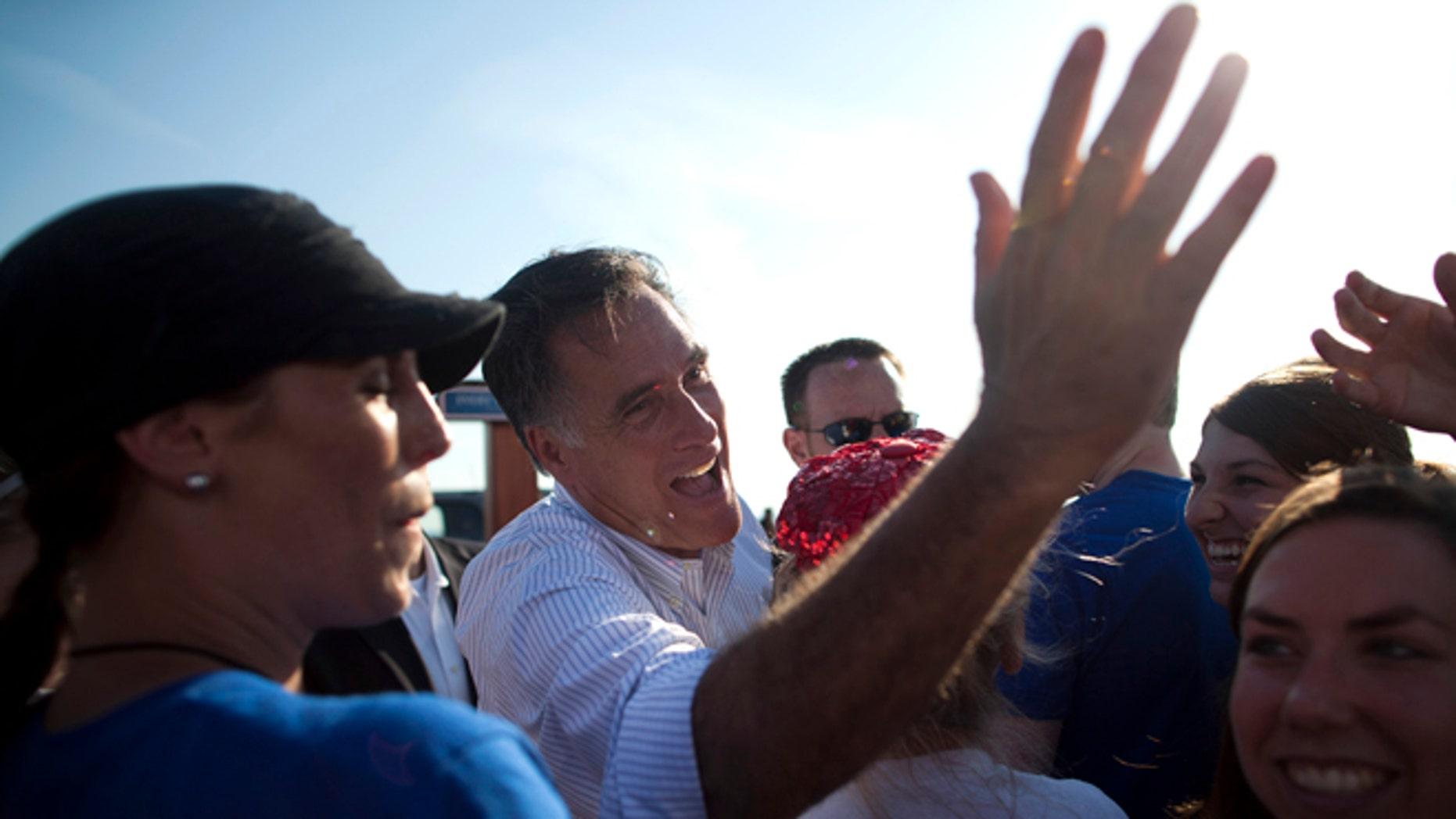 El virtual candidato presidencial republicano Mitt Romney saluda a partidarios durante un acto de campaña en el Holland State Park, el martes 19 de junio de 2012, en Holland, Michigan. (Foto AP/Evan Vucci)