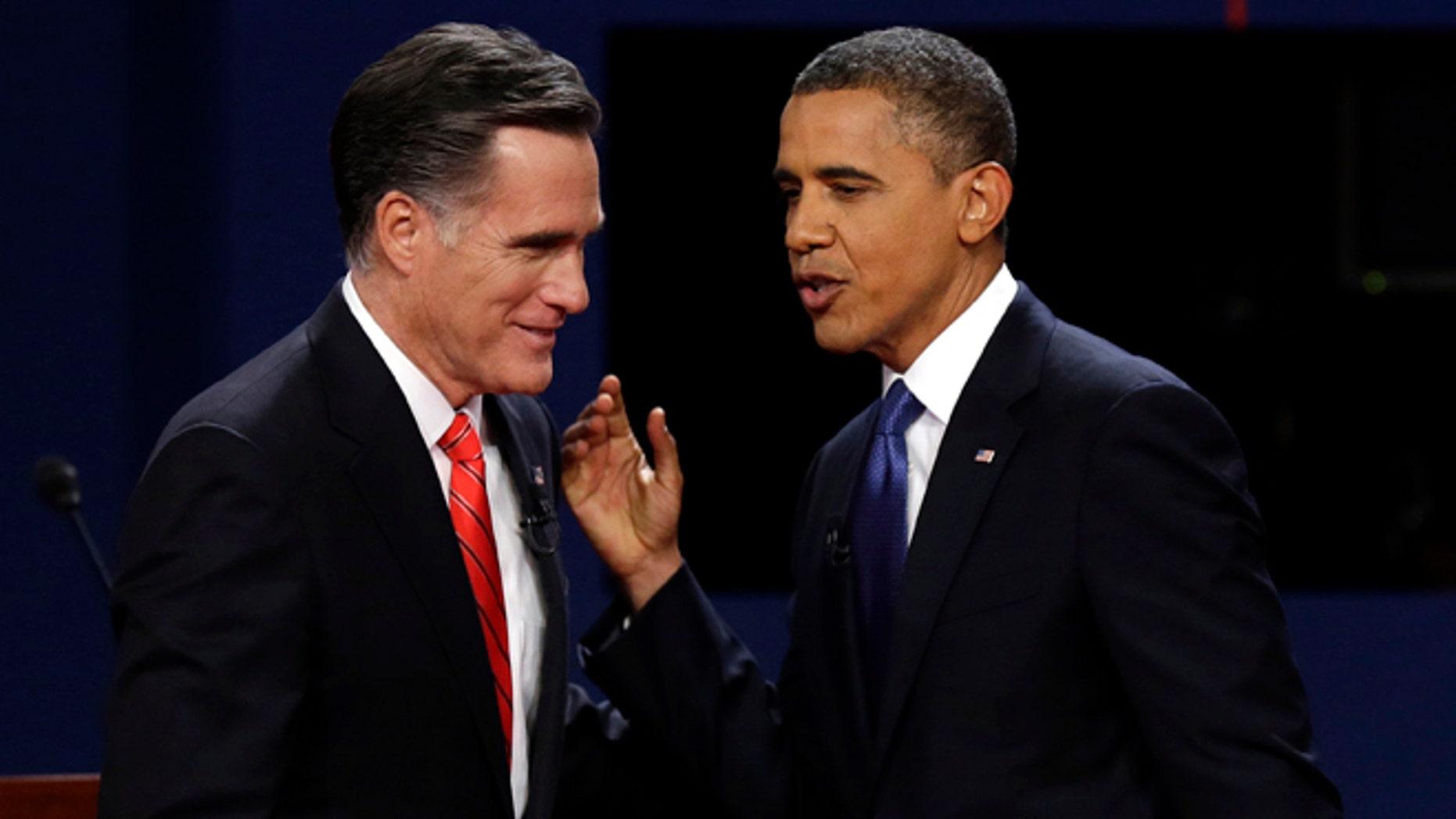 FILE: Oct. 3, 2012: Mitt Romney and President Obama talk after their debate at the University of Denver, in Denver.