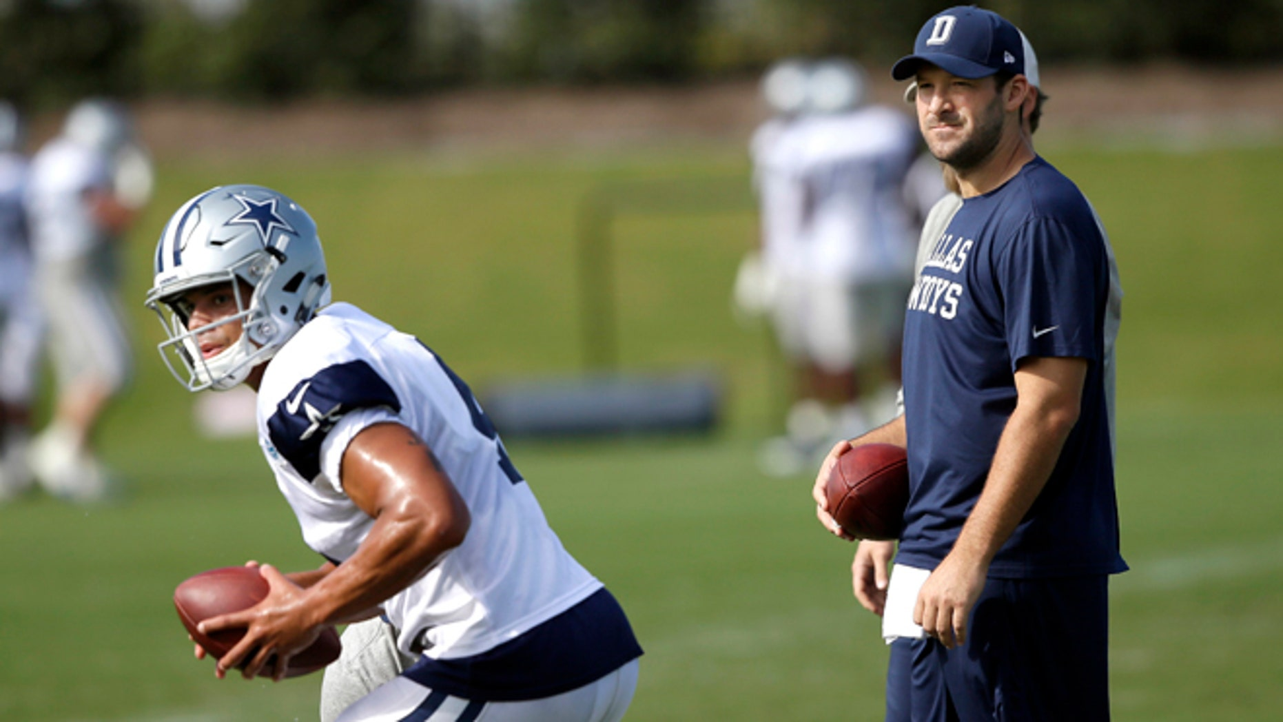 FILE - In this Oct. 26, 2016, file photo, Dallas Cowboys quarterback Tony Romo looks on as fellow quarterback Dak Prescott runs a drill during football practice at the team's practice facility in Frisco, Texas. Romo is running the scout team in practice even though Dallas' starting quarterback the past 10 years looks ready to return from a back injury. (AP Photo/LM Otero, File)