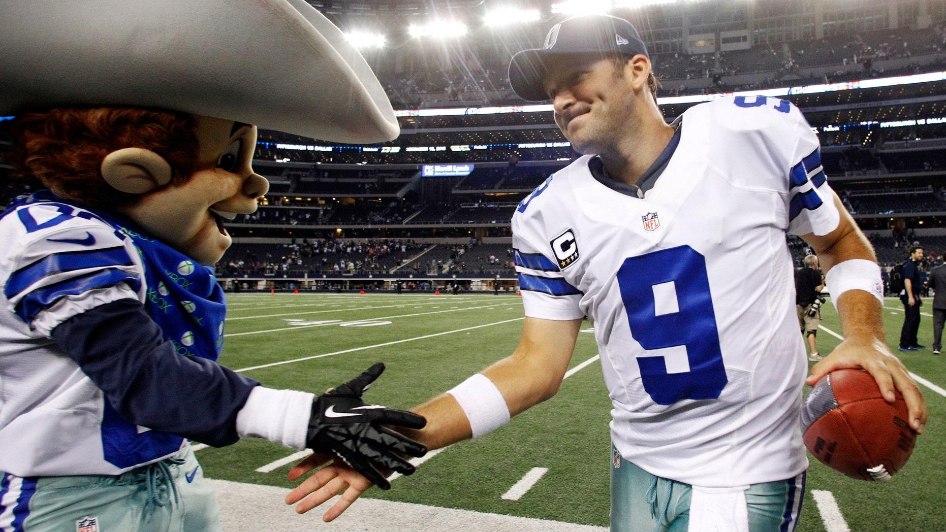 Dallas Cowboys quarterback Tony Romo (9) celebrates with team mascot Rowdy after defeating the Philadelphia Eagles 38-33 in an NFL football game Sunday, Dec. 2, 2012 in Arlington, Texas. (AP Photo/Tony Gutierrez)