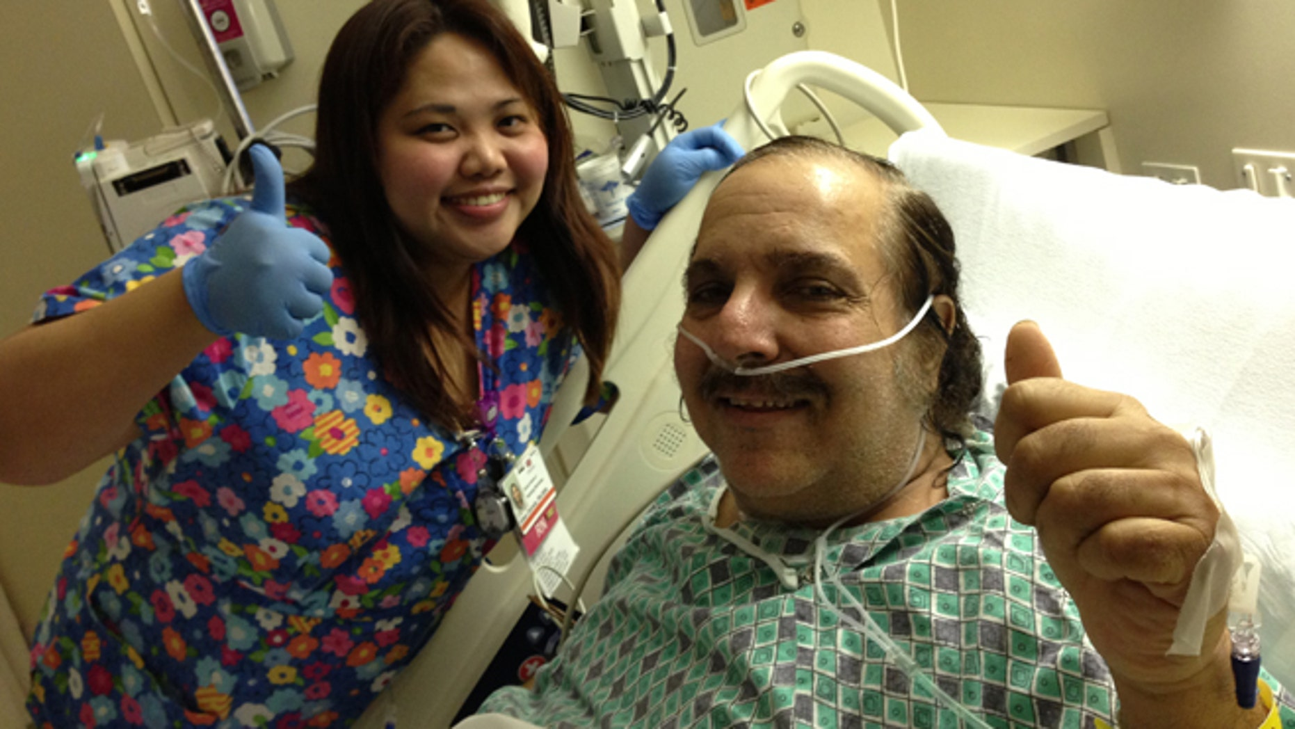 Ron Jeremy poses with one of his nurses while in the hospital.