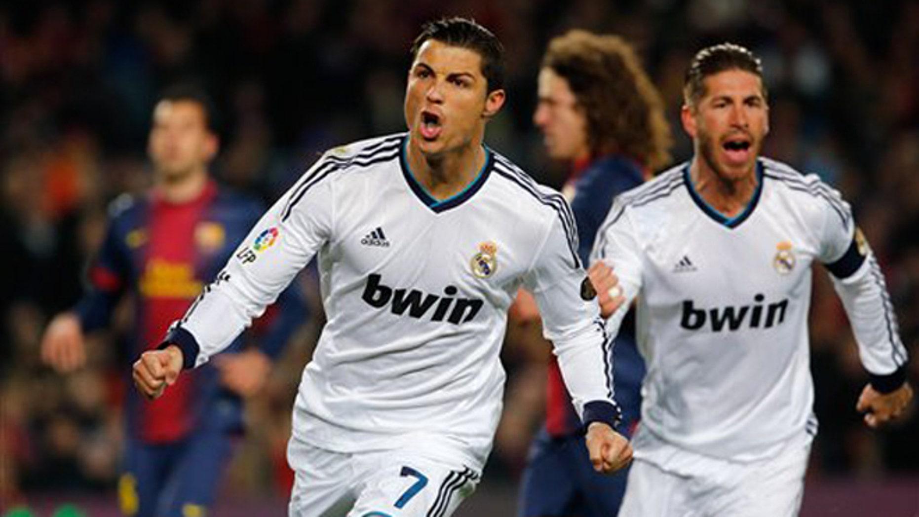 El jugador del Real Madrid, Cristiano Ronaldo, izquierda, festeja con su compañero Sergio Ramos, derecha, tras anotar un gol contra el Barcelona en la Copa del Rey el martes, 26 de febrero de 2013, en Barcelona.  (AP Photo/Emilio Morenatti)