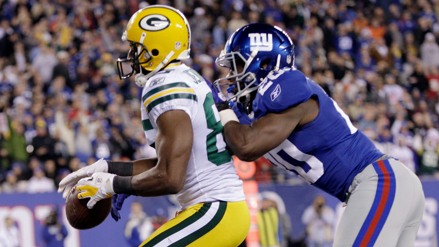 Green Bay Packers' Greg Jennings (85) catches a pass as New York Giants' Prince Amukamara (20) defends during the third quarter of an NFL football game Sunday, Dec. 4, 2011, in East Rutherford, N.J. The play was ruled a touchdown. (AP Photo/Kathy Willens)