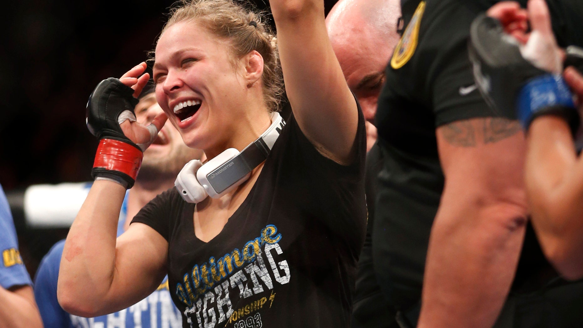 Ronda Rousey celebrates her win against Liz Carmouche after their UFC 157 women's bantamweight championship mixed martial arts match in Anaheim, Calif., Saturday, Feb. 23, 2013. Rousey won the first womenâs bout in UFC history, forcing Carmouche to tap out in the first round. (AP Photo/Jae C. Hong)