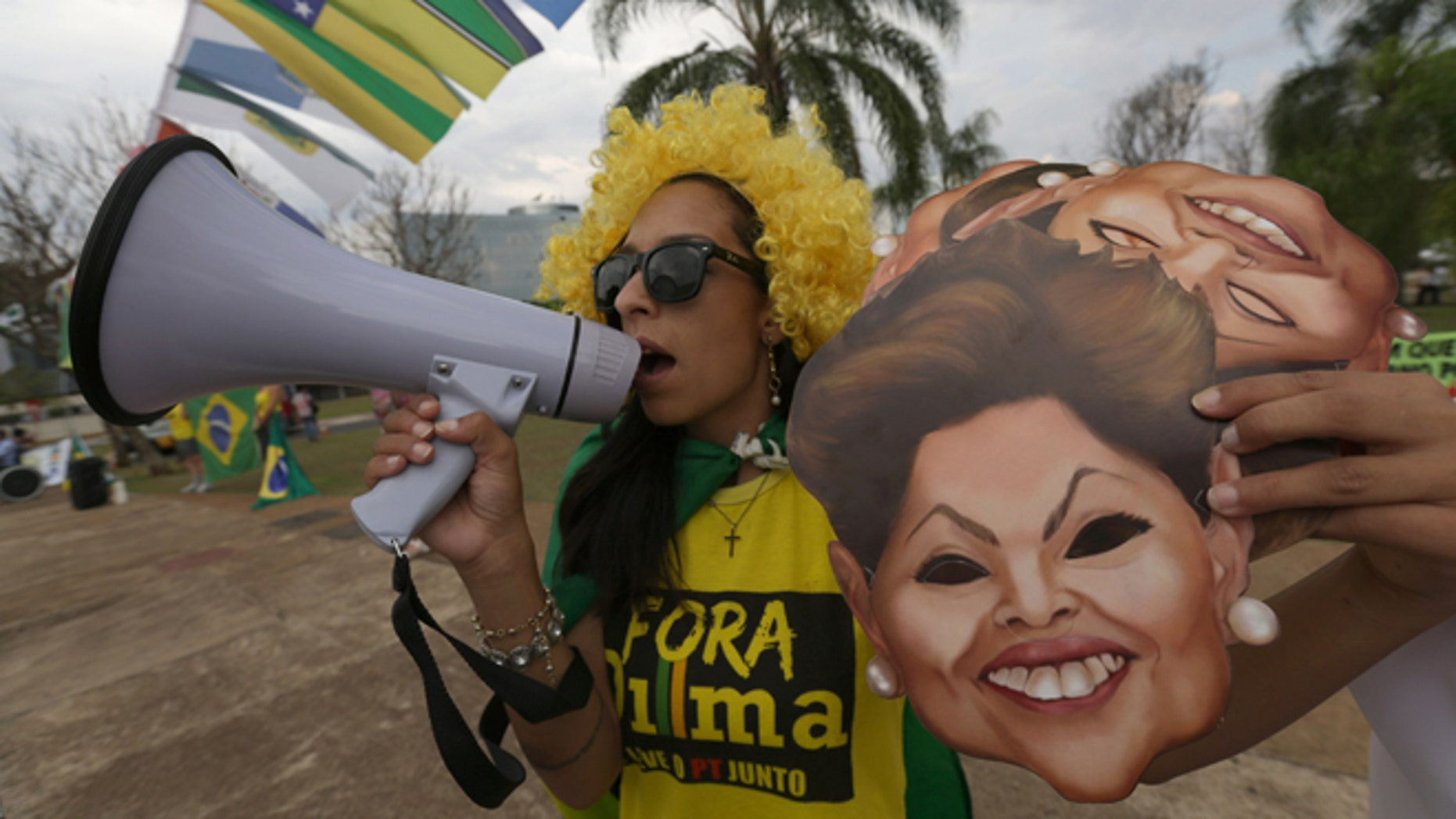 A demonstrator shouts slogans against Brazilian President Dilma Rousseff with a bullhorn outside the headquarters of the the Federal Court of Accounts in Brasilia, Brazil, Wednesday, Oct. 7, 2015. The Court decides today whether to approve the government accounts of the President Rousseff for 2011-214. Political opposition parties are accusing Rousseff of concealing information about her government's accounts. (AP Photo/Eraldo Peres)