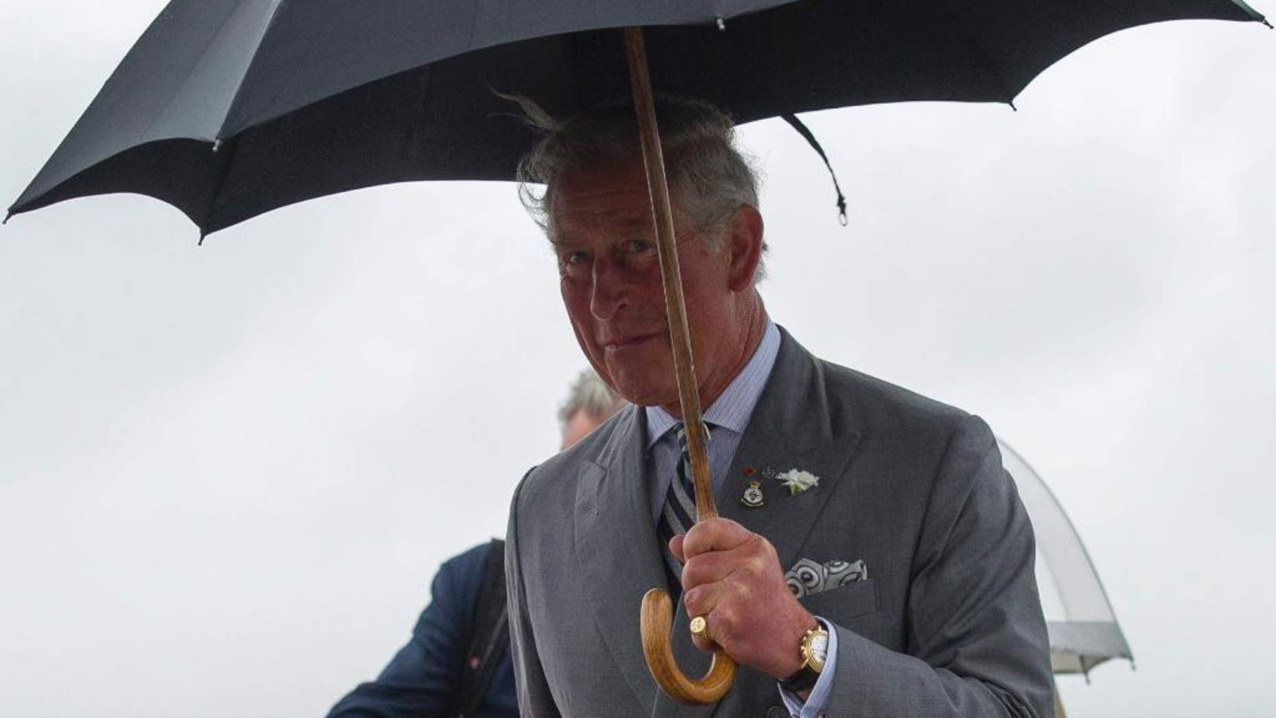 Prince Charles arrives in the rain at a Canadian Forces Base airport in Winnipeg, Canada, May 20, 2014 (AP Photo/The Canadian Press, David Lipnowski)