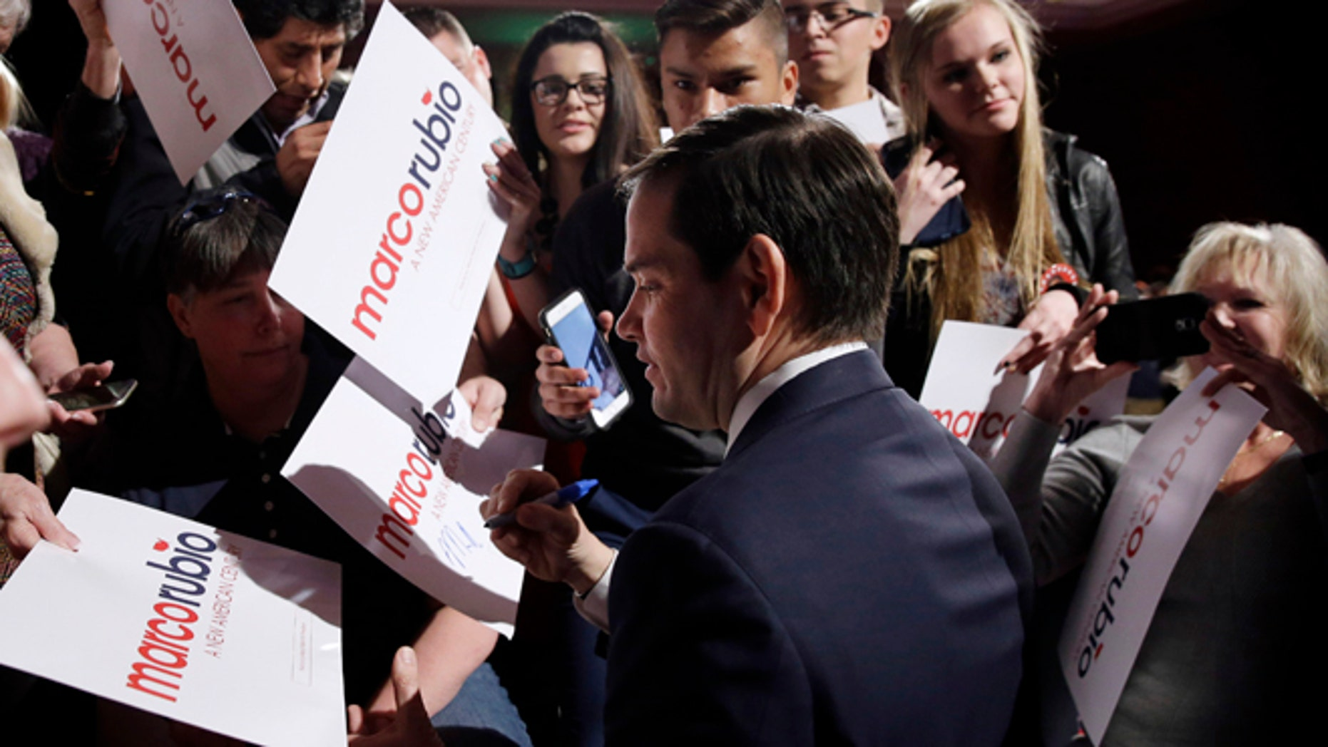 Republican presidential candidate Sen. Marco Rubio, R-Fla, center, signs autographs after speaking at a rally Monday, Feb. 22, 2016, in Reno, Nev. (AP Photo/Marcio Jose Sanchez)