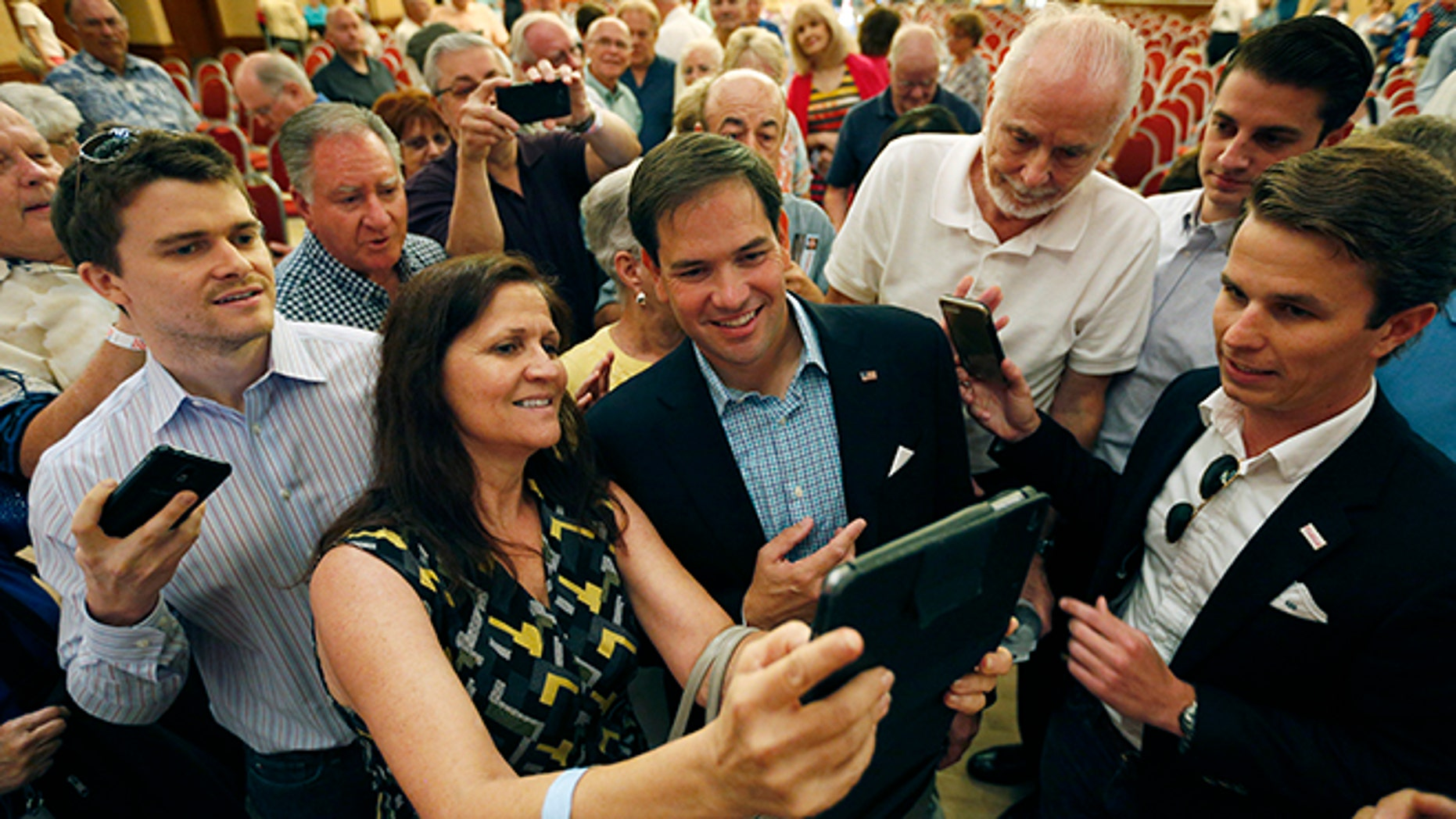 Republican presidential candidate Sen. Marco Rubio, R-Fla., takes pictures with people during a campaign event Saturday, July 11, 2015, in Henderson, Nev. (AP Photo/John Locher)