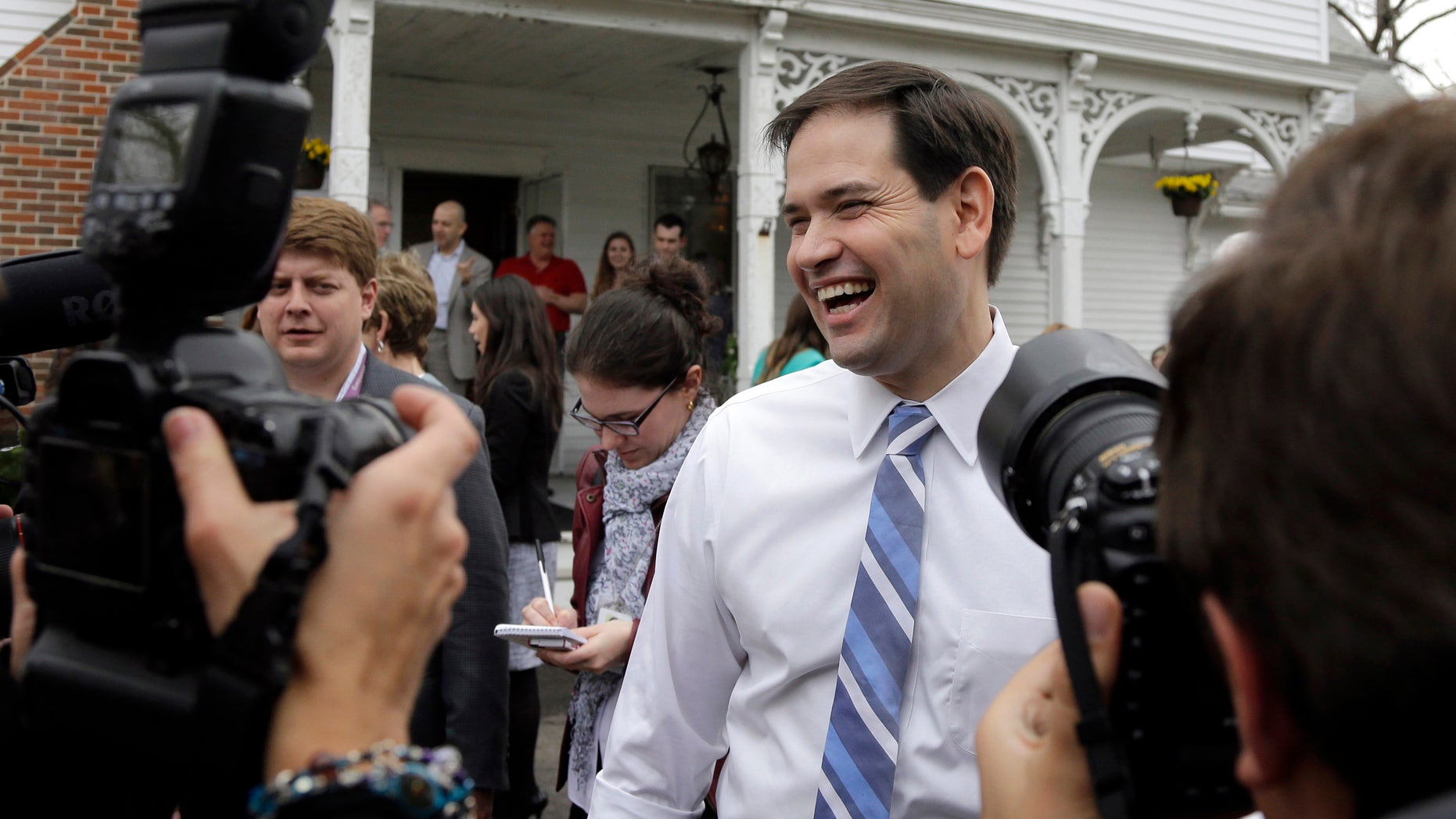 In this April 17, 2015 photo, Republican presidential candidate, Sen. Marco Rubio, R-Fla., laughs as he is surrounded by media at a campaign house party in Manchester, N.H. Devoted political allies for more than a decade, the alliance between former Florida Gov. Jeb Bush and Rubio is beginning to splinter as the one-time mentor and his political protégé face off in the race for the Republican presidential nomination. (AP Photo/Elise Amendola)