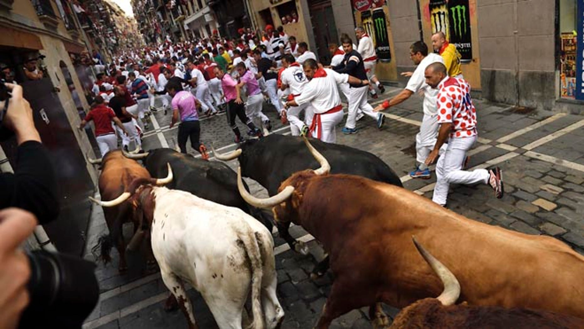 Revelers run in front of Jandilla's fighting bulls at the San Fermin Festival, in Pamplona, Monday, July 11, 2016.