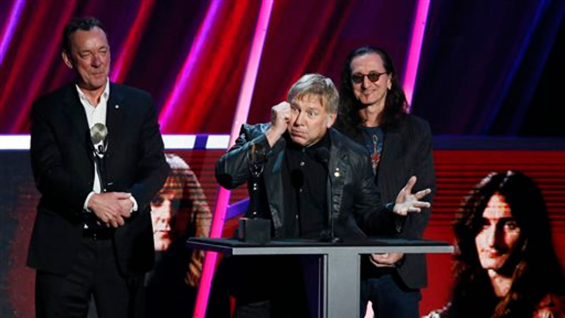 Alex Lifeson, center, Neil Peart, left, and Geddy Lee, right, of Rush accept their band's induction into the Rock and Roll Hall of Fame during the Rock and Roll Hall of Fame Induction Ceremony at the Nokia Theatre on Thursday, April 18, 2013 in Los Angeles.