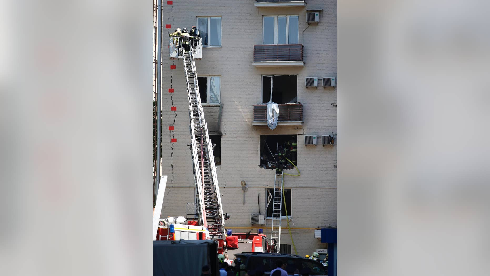 Firefighters on a ladder mark a big crack on the wall of a damaged apartment building after an explosion in downtown Moscow, Thursday, May 22, 2014. The apartment building in downtown Moscow was damaged by an explosion, which officials said was caused by a natural gas leak. (AP Photo/ Pavel Golovkin)