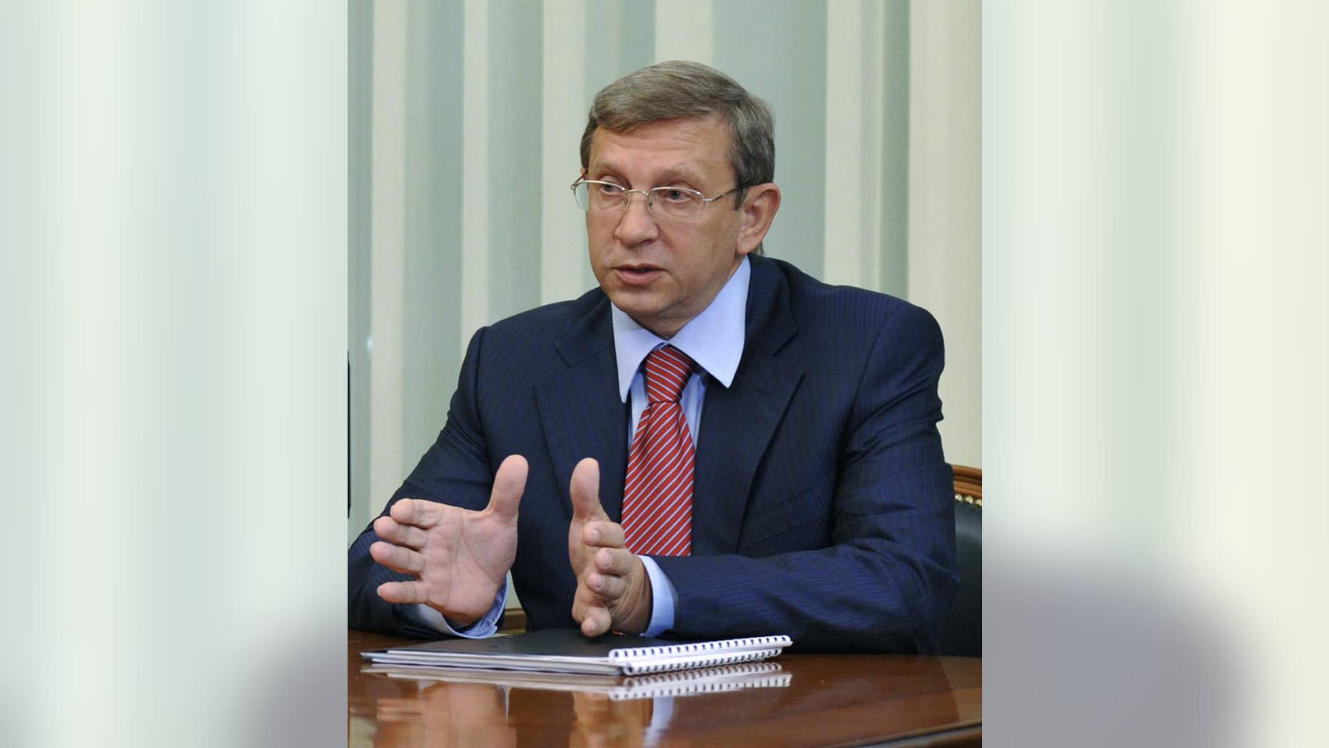 FILE-  In this Tuesday, May 5, 2009 file photo Russian tycoon Vladimir Yevtushenkov, owner of Sistema Holding, speaks during a meeting with then Russian Prime Minister Vladimir Putin in Moscow, Russia. The arrest of the Russian billionaire has sent shares in his holding company into a tailspin Wednesday morning, Sept. 17, 2014. Yevtushenkov, who is worth $9 billion according to the Russian Forbes magazine, was placed under house arrest late Tuesday, Sept. 16, in a money-laundering case which has drawn comparisons with a government crackdown on the Yukos oil company more than a decade ago. (AP Photo/RIA Novosti, Alexei Druzhinin, Presidential Press Service, File)