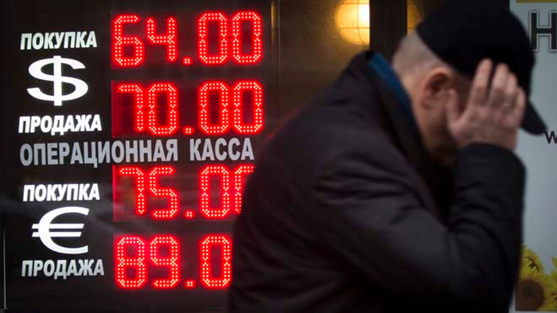 Dec. 16, 2014: Signs advertising currencies light next to the exchange office in Moscow, Russia. After a massive overnight rate hike by Russia's Central Bank, the ruble staged a two-hour rally Tuesday morning before rolling back to new historic lows.