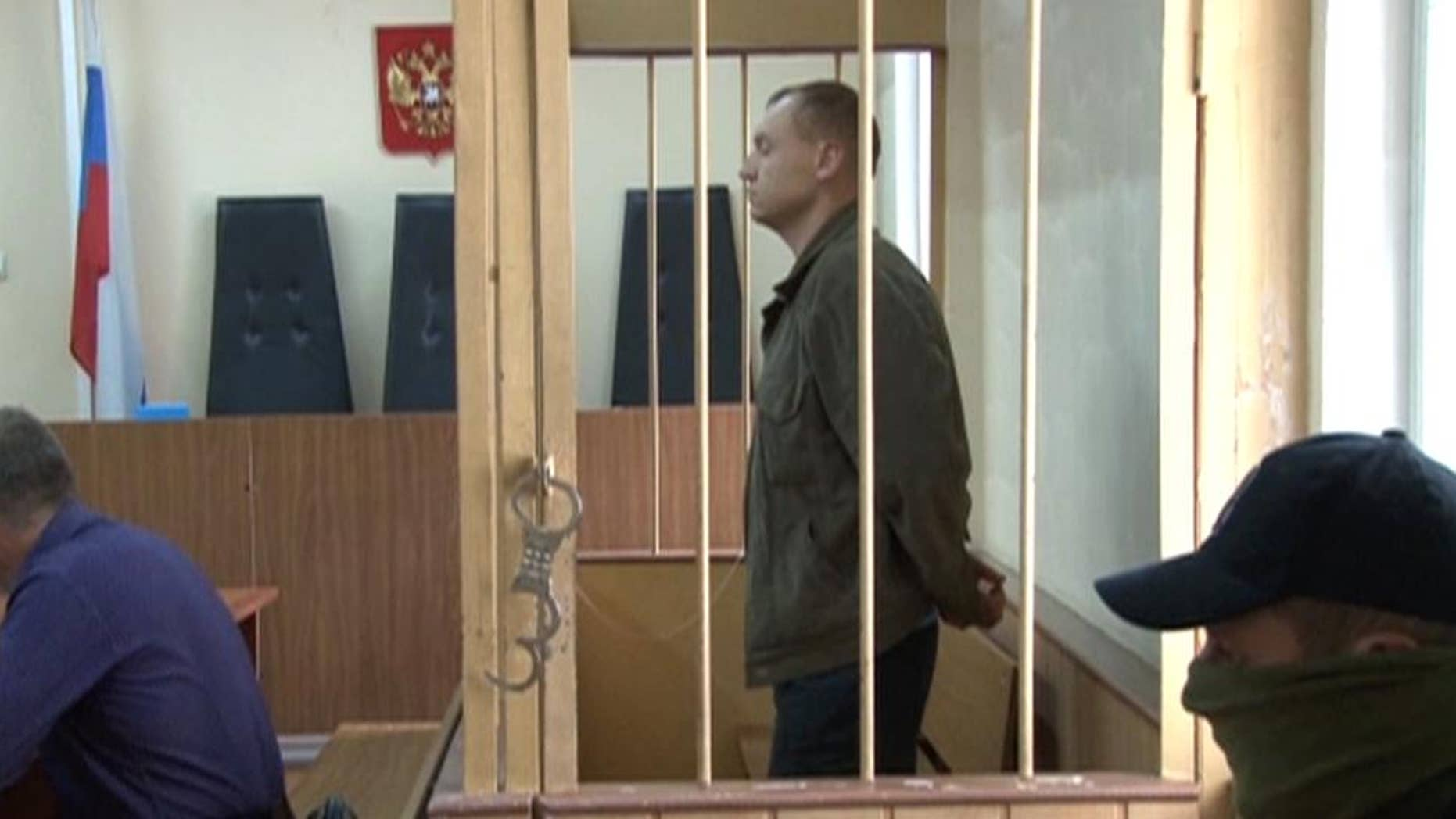 In this September 17, 2014 video grab made available by the APTN on Wednesday, Aug. 19, 2015 Eston Kohver of Estonia stands behind bars in Pskov, Russia. The regional court in the western city of Pskov on Wednesday, Aug. 19, 2015, found Kohver guilty of spying, arms smuggling and violating border regulations and ruled to send him to a high-security prison for 15 years. (AP Photo/APTN) TV OUT RUSSIA OUT