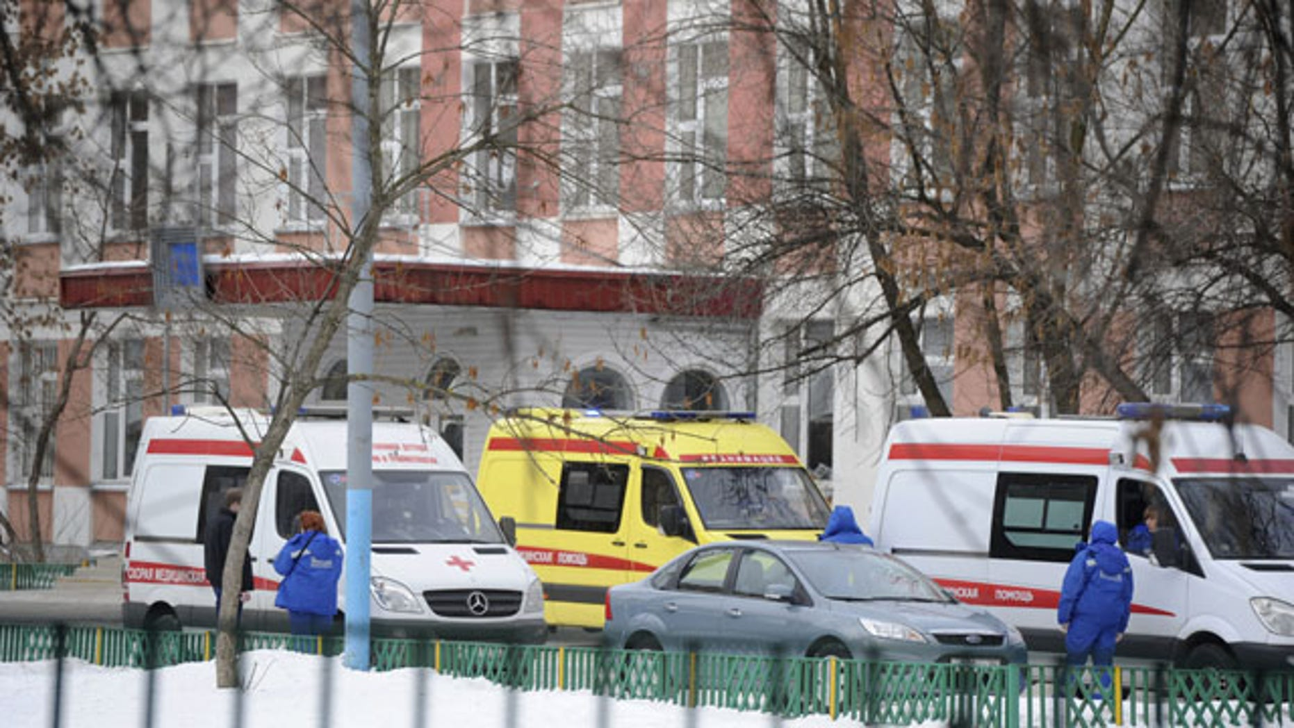 February 3, 2014: Ambulances are parked at an entrance to a school in Moscow, Russia. Moscow police said an armed teenager burst into the school and killed a security guard and a teacher before being taken into custody. (AP Photo/Anton Belitsky)