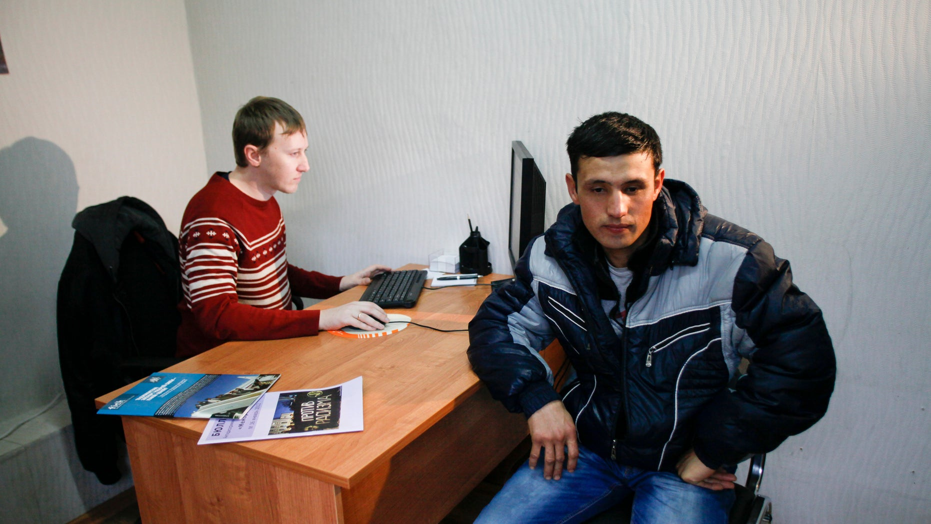 Jan. 30, 2013: In this photo Eshkobil Ashurov visits a consultancy for migrant workers in Sochi run by Semyon Simonov, left.