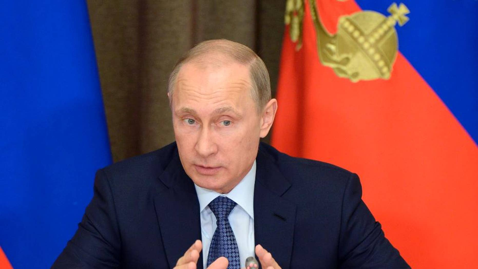 """FILE - In this May 12, 2015 file photo, Russian President Vladimir Putin speaks at a meeting with representatives of top military brass and defense industries at the Bocharov Ruchei residence in the Black Sea resort of Sochi, Russia. Putin signed a bill into law Saturday, May 23, 2015, giving prosecutors the power to declare foreign and international organizations """"undesirable"""" in Russia and shut them down. (Alexei Nikolsky/RIA-Novosti, Kremlin Pool Photo via AP, File)"""