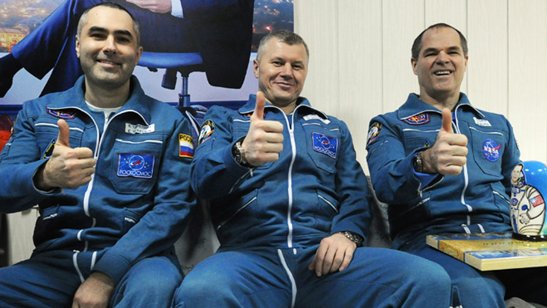 March 16, 2013: Russian cosmonauts Yevgeny Tarelkin, left, Oleg Novitsky, center, and NASA's astronaut Kevin Ford pose for a photo at the airport of the Kazakh city of Kostanai after their landing in northern Kazakhstan.