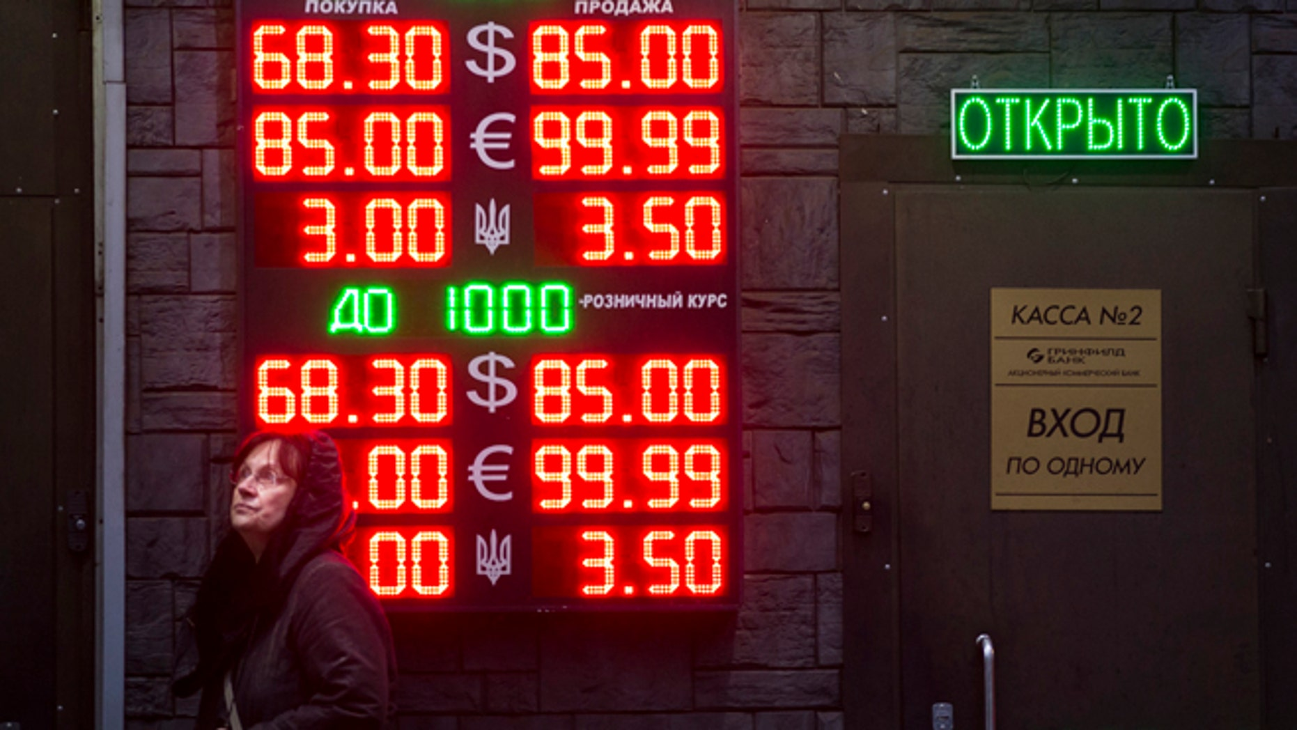 Dec. 16, 2014: People wait to exchange currency near a sign advertising currency exchange rates at an exchange office in Moscow, Russia.