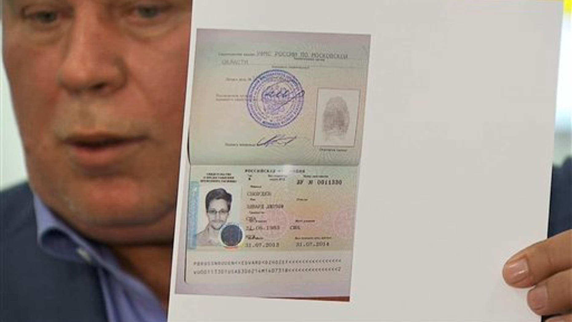 Aug. 1, 2013 -  Russian lawyer Anatoly Kucherena showing a temporary document to allow National Security Agency leaker Edward Snowden to cross the border into Russia while speaking to the media after visiting Snowden at Sheremetyevo airport outside Moscow, Snowden has received asylum in Russia for one year and left the transit zone of Moscow's airport, his lawyer said Thursday. (image taken from APTV.)