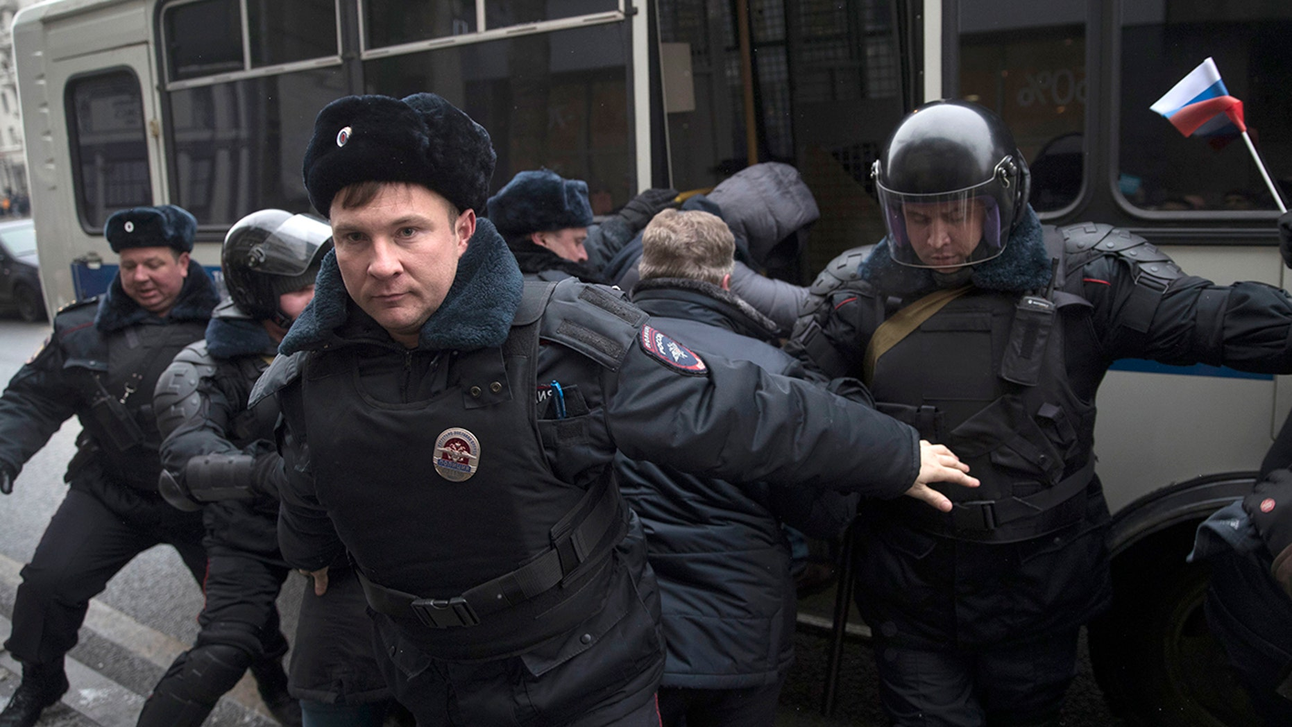 Russian opposition leader Alexei Navalny, in the background, is detained by police officers in Moscow, Russia, Sunday.