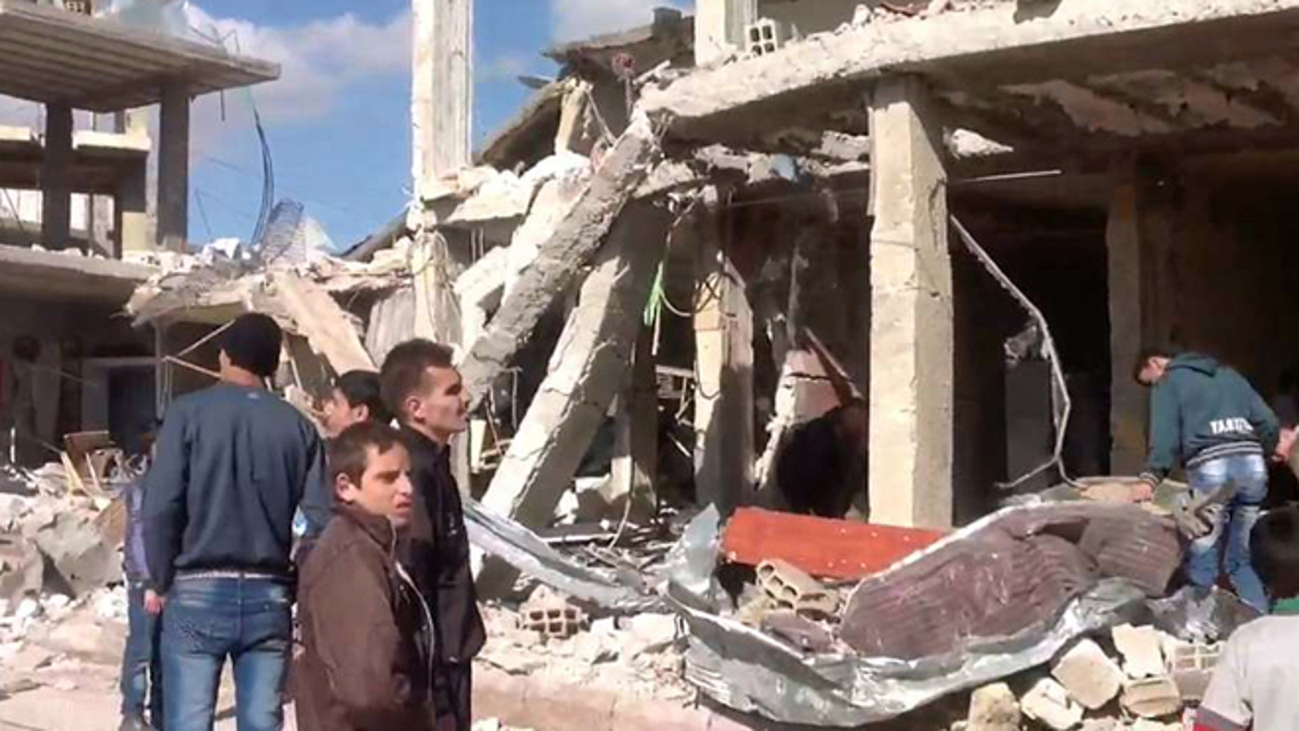 Dec. 13, 2012: In this photo released by the Syrian official news agency SANA, Syrian citizens gather in front of a damaged building destroyed by a car bomb in Qatana, 15 miles southwest of Damascus, Syria.