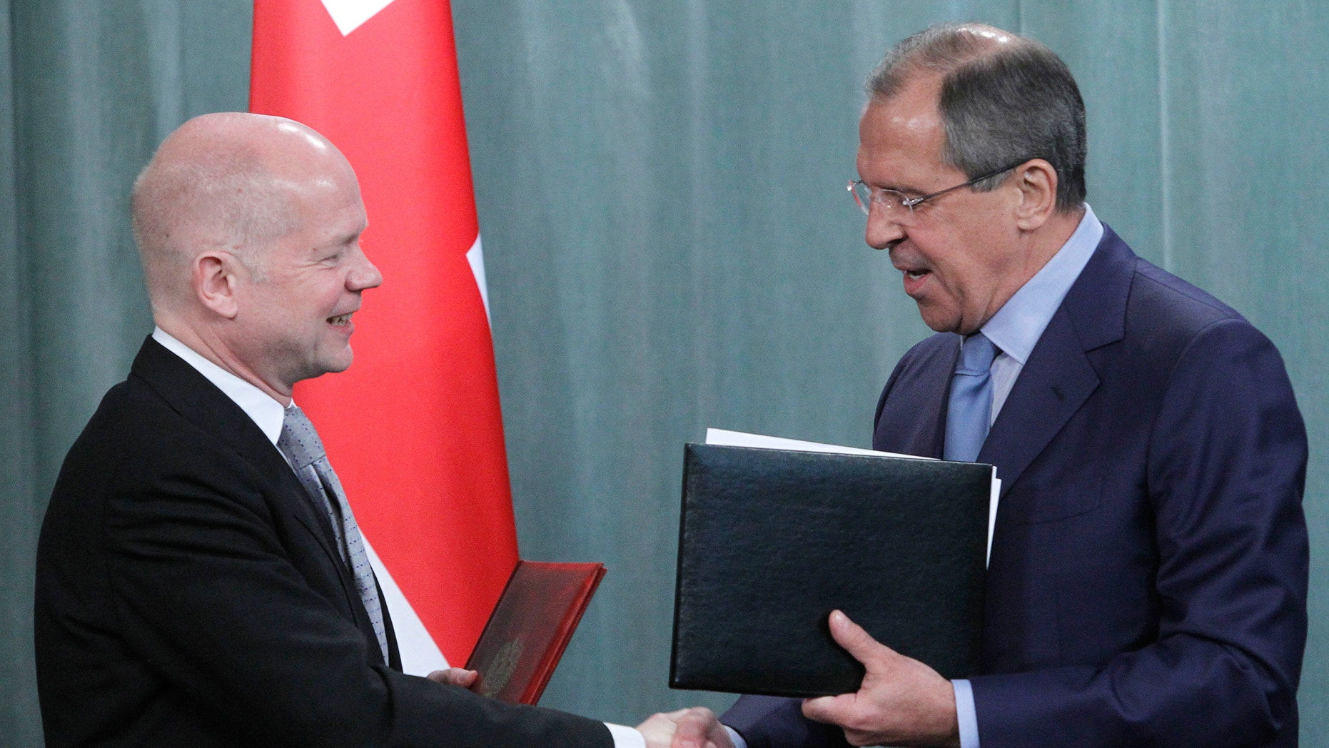 May 27, 2012: Russian Foreign Minister Sergey Lavrov, right, and his British counterpart William Hague shake hands as they exchange documents after their meeting in Moscow, Russia.