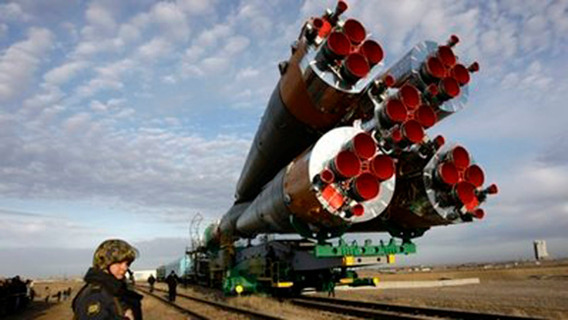 A Russian police officer guards the Russian Soyuz TMA-18 space ship getting transported from a hangar to the launch pad at the Russian leased Baikonur Cosmodrome, Kazakhstan.