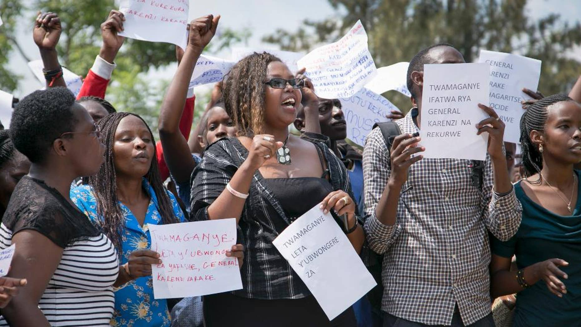 """Protesters calling for the release of Lt. Gen. Karenzi Karake, who serves as Rwanda's spy chief, demonstrate outside the British High Commission in Kigali, Rwanda Wednesday, June 24, 2015. Hundreds of people demonstrated outside the British High Commission in Rwanda saying they will not return home until Karake, who was detained in the UK, is set free. Placards in front row in Kinyarwanda from left to right read """"We protest the government of United Kingdom which arrested General Karenzi Karake"""", """"We protest the government of United Kingdom"""" and """"We protest the arrest of General Karenzi; free him."""" (AP Photo/Denyse Uwera)"""