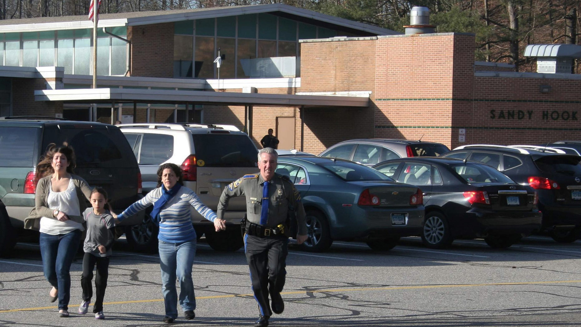 A police officer leads two women and a child from Sandy Hook Elementary School in Newtown, Conn., on Friday,  Dec. 14, 2012.