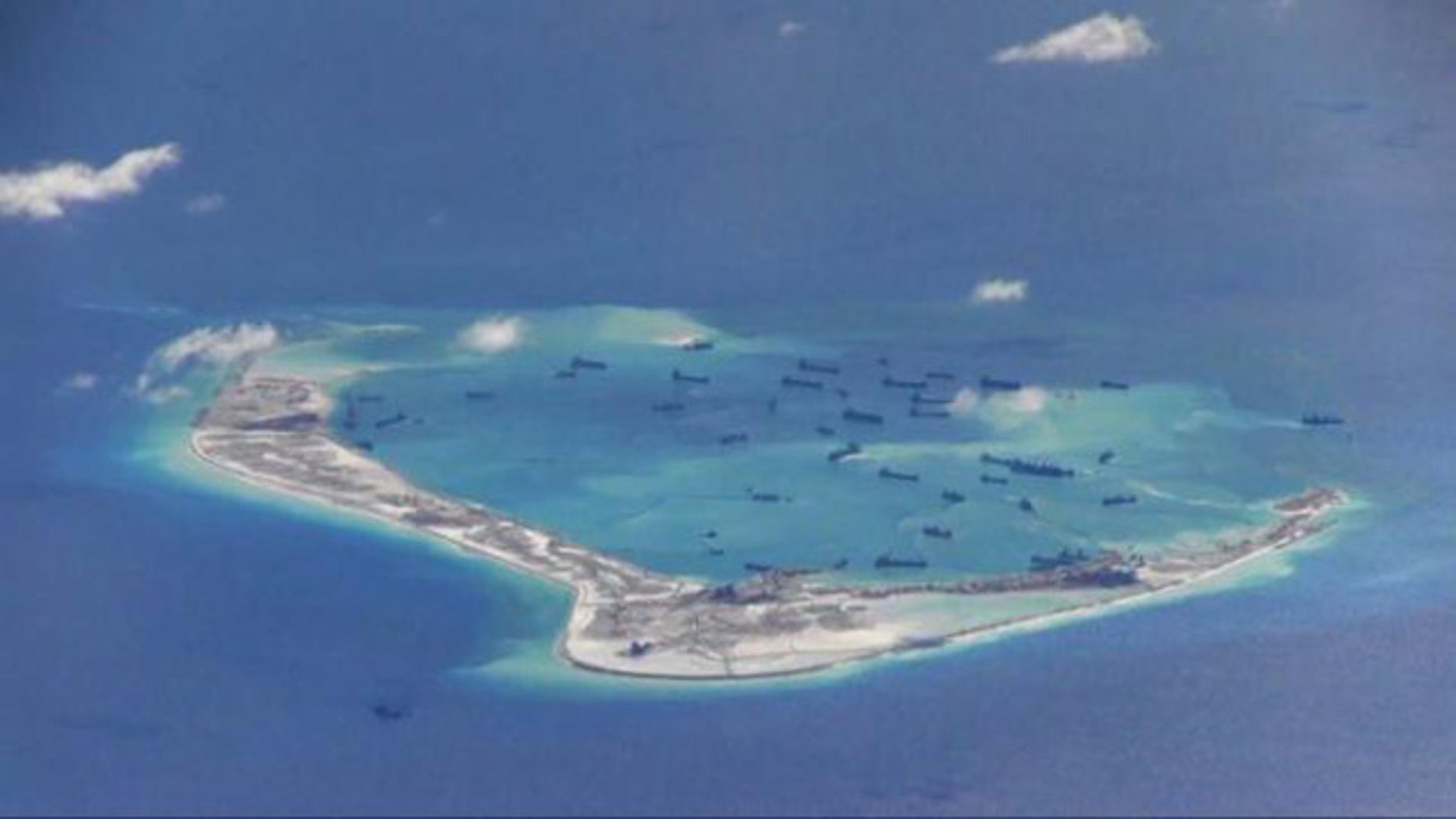 May 21, 2015: Chinese dredging vessels are purportedly seen in the waters around Mischief Reef in the disputed Spratly Islands in the South China Sea in this still image from video taken by a P-8A Poseidon surveillance aircraft. (U.S. Navy)