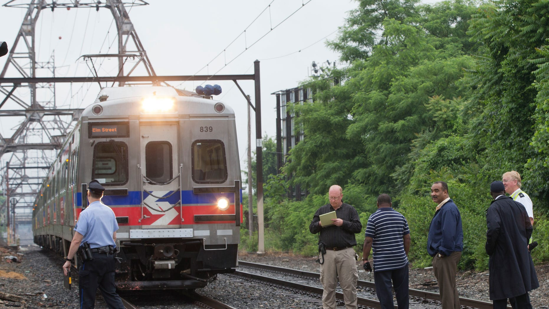 June 9, 2014: Officials stand near an idle Southeastern Pennsylvania Transportation Authority train.