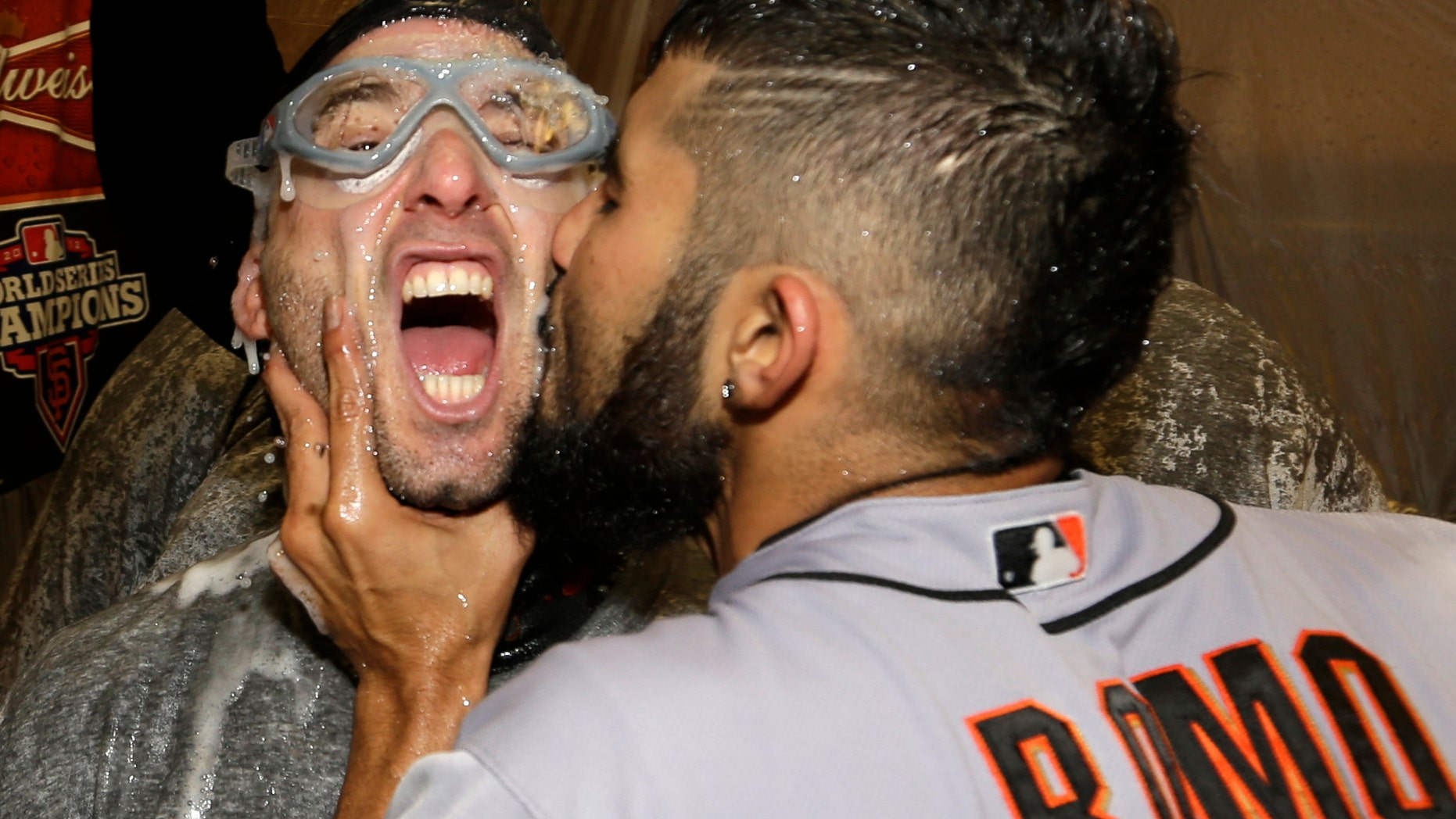 Sergio Romo kisses Marco Scutaro as they are sprayed with champagne in the locker room as San Francisco Giants celebrate after the Giants defeated the Detroit Tigers, 4-3, in Game 4 of baseball's World Series  Sunday, Oct. 28, 2012, in Detroit. The Giants won the World  Series 4-0. (AP Photo/David J. Phillip)