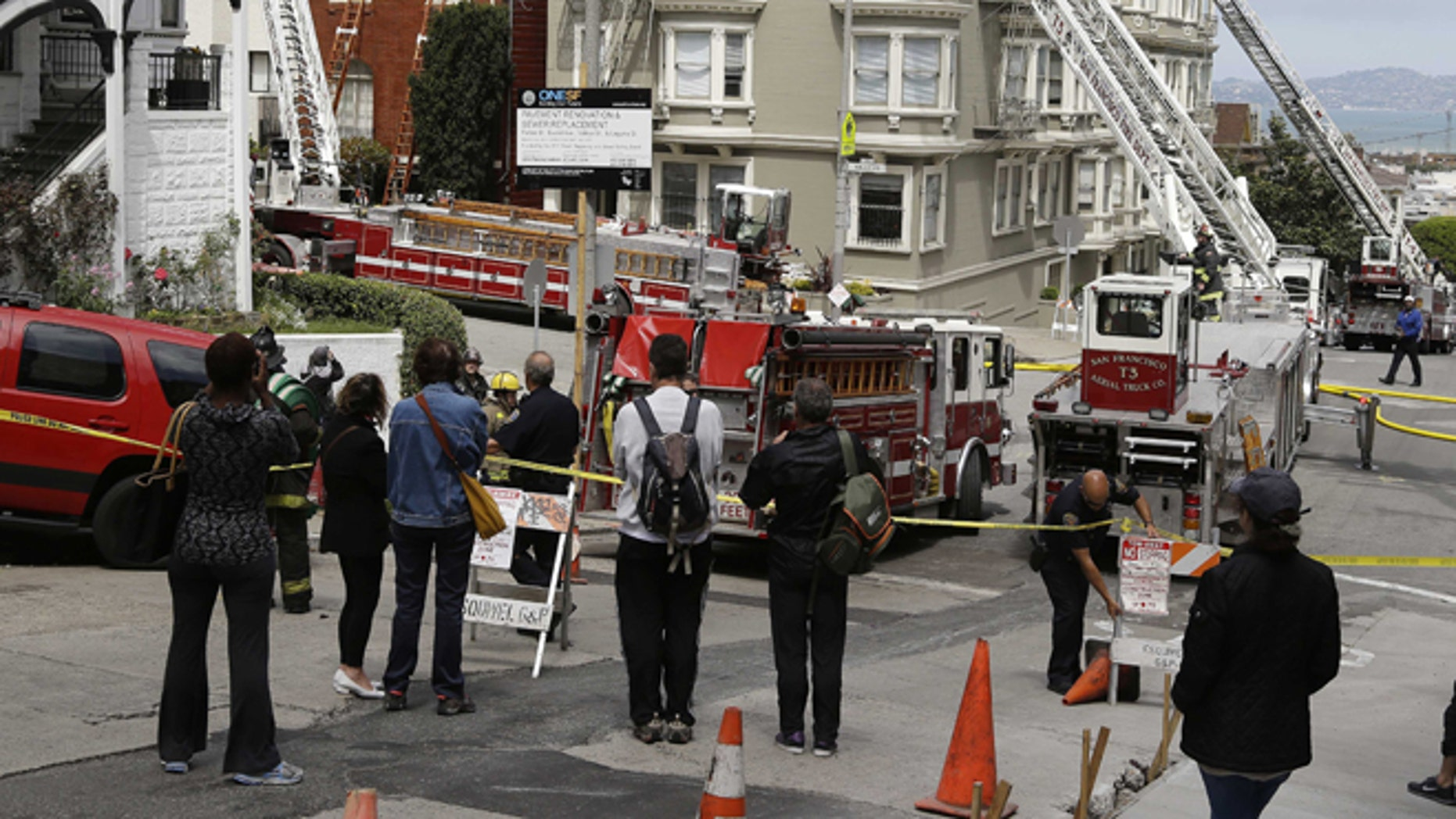 April 24: People watch firemen contain a fire at a multi-unit building at left following a fire in San Francisco.