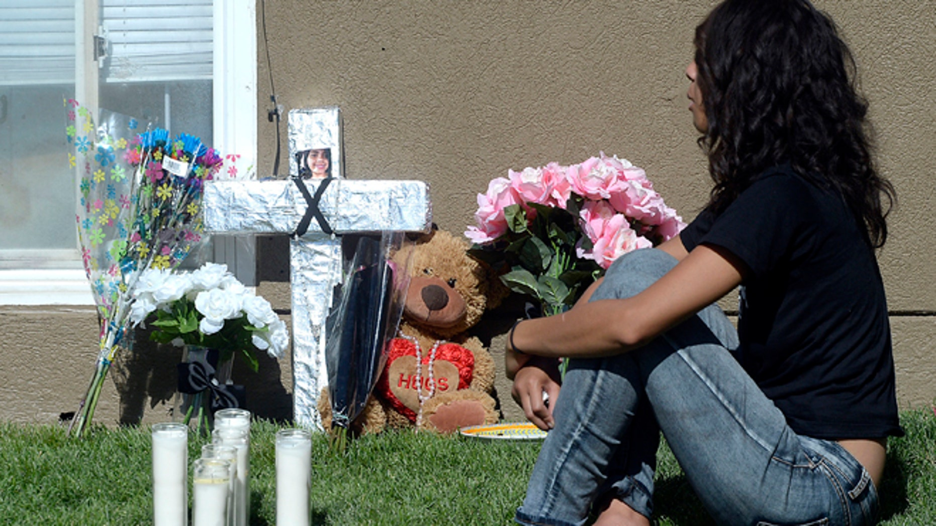 Friends and family mourn at a memorial for sixteen-year-old Jose Izazaga and his 15-year-old sister Abril Izazaga, Thursday, July 7, 2016 in Midvale, Utah. As police search for a man who police say gunned down a teenage brother and sister during an argument over a T-shirt late Wednesday at a Salt Lake City suburb apartment complex, family members are mourning the senseless killing of siblings who shared a tight bond. (Al Hartmann/The Salt Lake Tribune via AP)