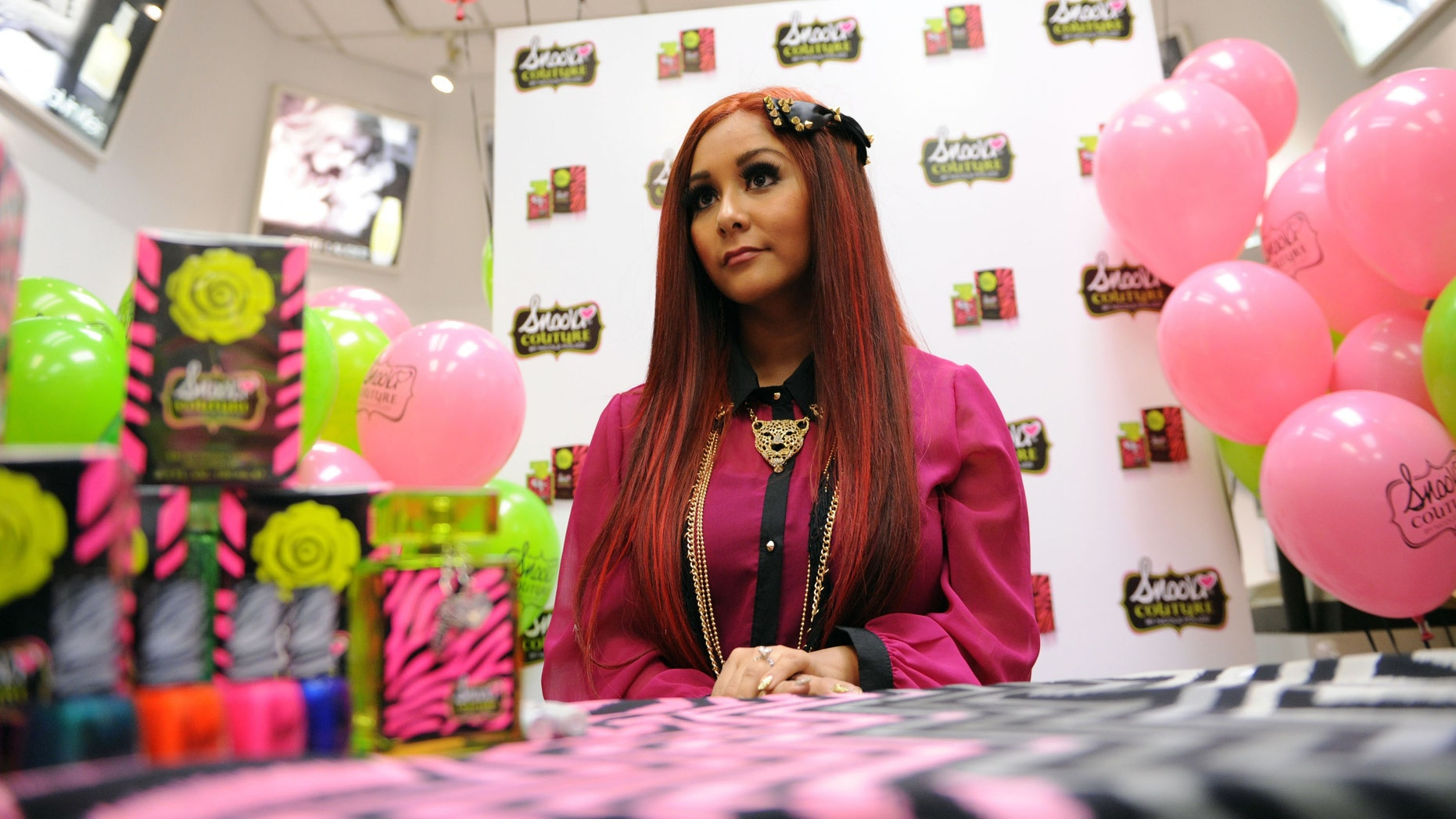 "NEW YORK, NY - NOVEMBER 19:  Nicole ""Snooki"" Polizzi autographs her Snooki Couture Fragrance at Perfumania NYC on November 19, 2012 in New York City.  (Photo by Bryan Bedder/Getty Images for Perfumania)"