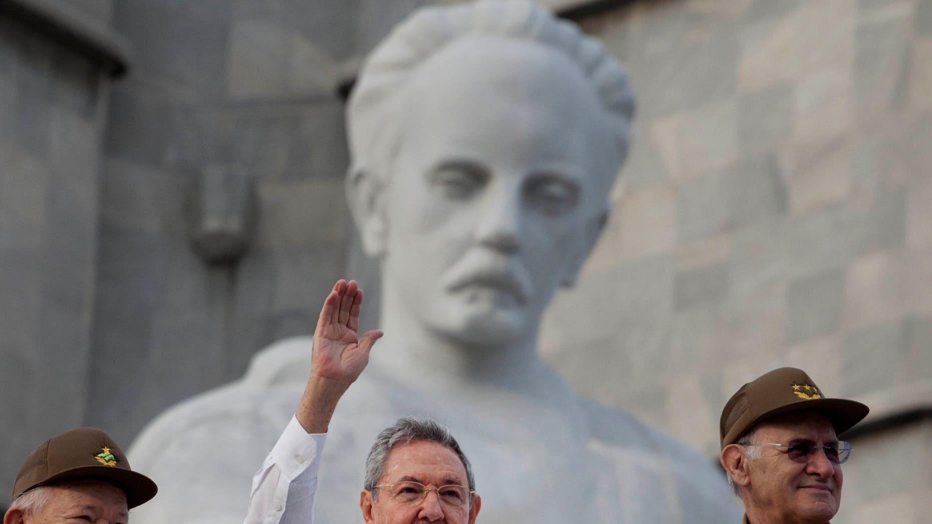 El presidente cubano Raúl Castro, al centro, saluda a las personas que participan en la marcha por el Día del Trabajo, en la Plaza de la Revolución, en La Habana, el 1 de mayo de 2013. Washington no tiene planes de quitar a Cuba de la lista de gobiernos que apoyan al terrorismo y que también incluye a Irán, Siria y Sudán, dijo el miércoles un portavoz del Departamento de Estado. (Foto AP/Ramon Espinosa)