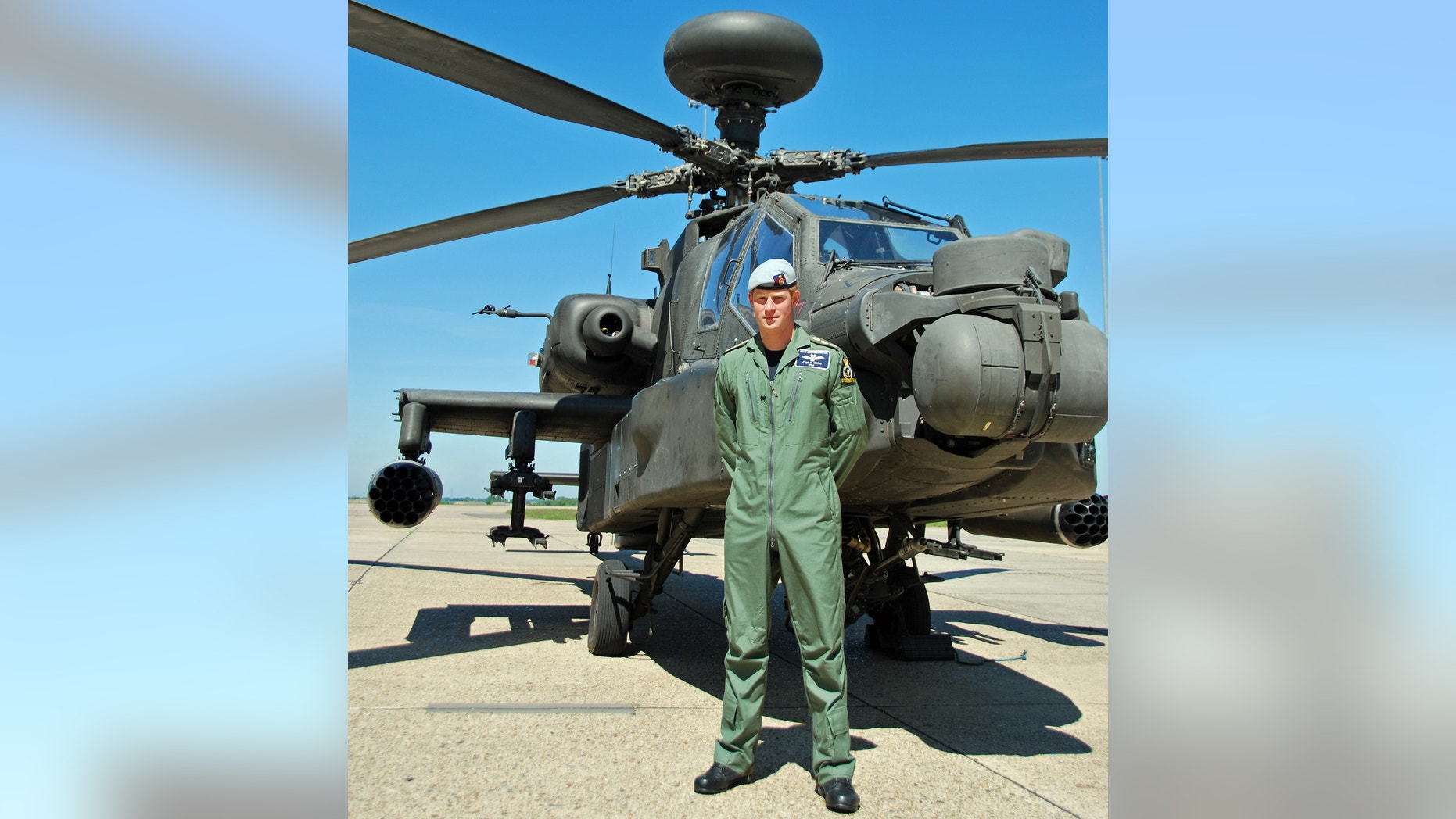 Photo released Friday July 5, 2013 shows Britain's Prince Harry posing in front of an Apache helicopter in an undisclosed location. Prince Harry has this week qualified as an Apache Aircraft Commander, the culmination of his training over the last three years.