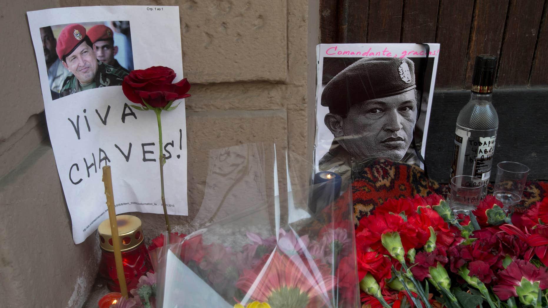 Velas, flores y una botella de vodka rodean la imagen del difunto presidente venezolano Hugo Chávez frente a la embajada venezolana en Moscú, miércoles 6 de marzo de 2013. (AP Foto/Misha Japaridze)