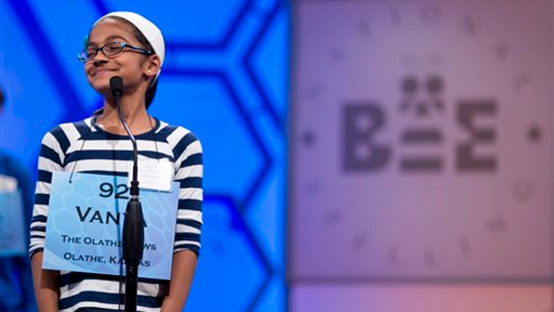 This May 30, 2012, file photo shows Vanya Shivashankar, of Olathe, Kan., smiling as she answers her question during the third round of the National Spelling Bee in Oxon Hill, Md. (AP Photo/Evan Vucci, File)