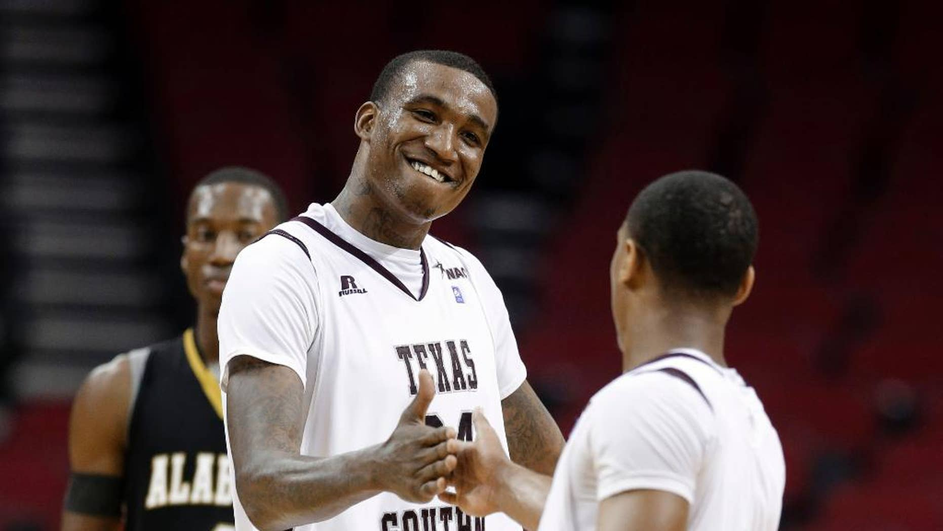 Texas Southern's Aaric Murray (24) celebrates with Madarious Gibbs (3) after Texas Southern defeated Alabama State in an NCAA college basketball game in the semifinals of the Southwestern Athletic Conference men's tournament Friday, March 14, 2014, in Houston. Texas Southern won 73-61. (AP Photo/David J. Phillip)