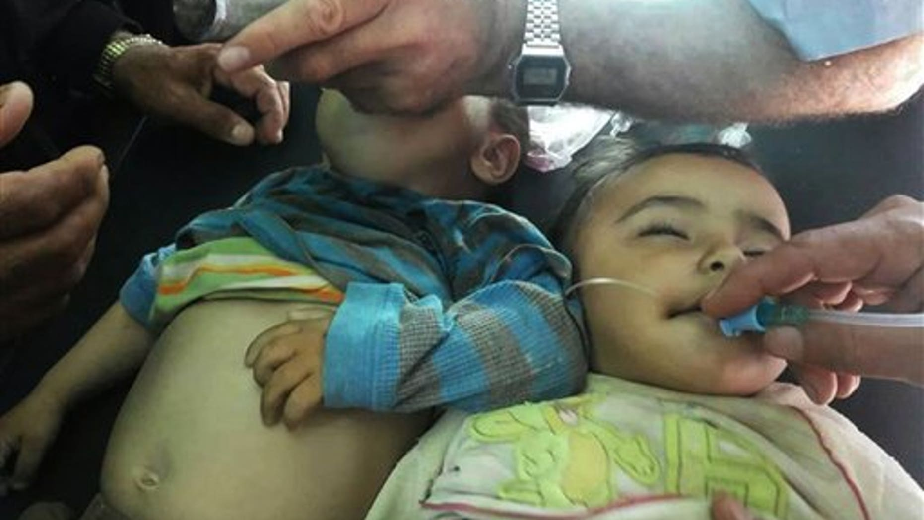 Sept. 17, 2014: Two Syrian children receive treatment after they were given a second round of measles vaccinations, in Idlib province. At least 15 children died after receiving vaccinations in rebel-held parts of Syria.