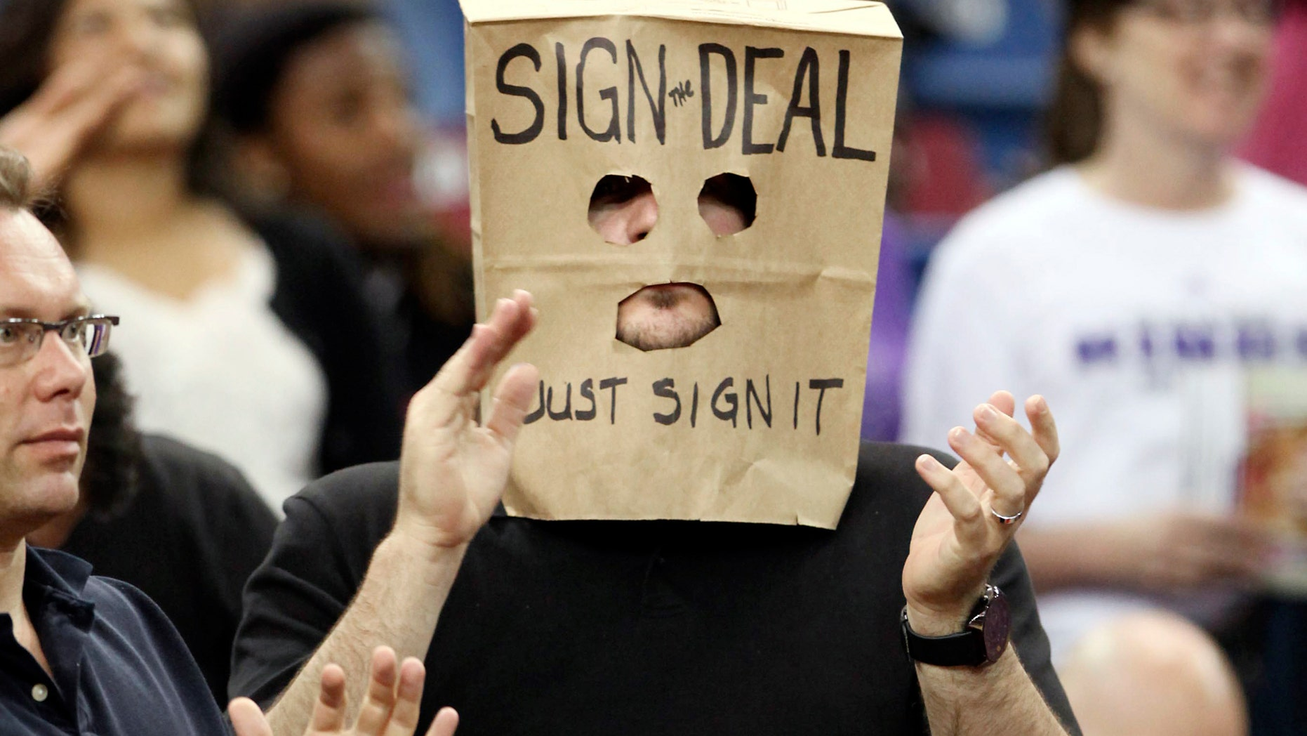 A Sacramento Kings fan wears a bag over his head calling for the Maloof family, owners of the team, to sign an arena deal during an NBA basketball game against the Portland Trail Blazers in Sacramento, Calif., Sunday, April 15, 2012.7  A plan to build a new arena for the team fell through last Friday leaving Kings fans wondering about the future of the team. (AP Photo/Rich Pedroncelli)
