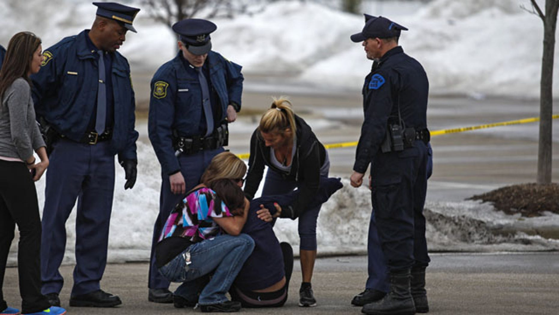 March 11, 2014: Skye Cieszlak, girlfriend of missing Saginaw Spirit hockey player Terry Trafford, is comforted after collapsing in the parking lot of the Saginaw Township Wal-Mart. Police found Trafford's body in an SUV in the parking lot (AP Photo/The Saginaw News, Neil Barris)