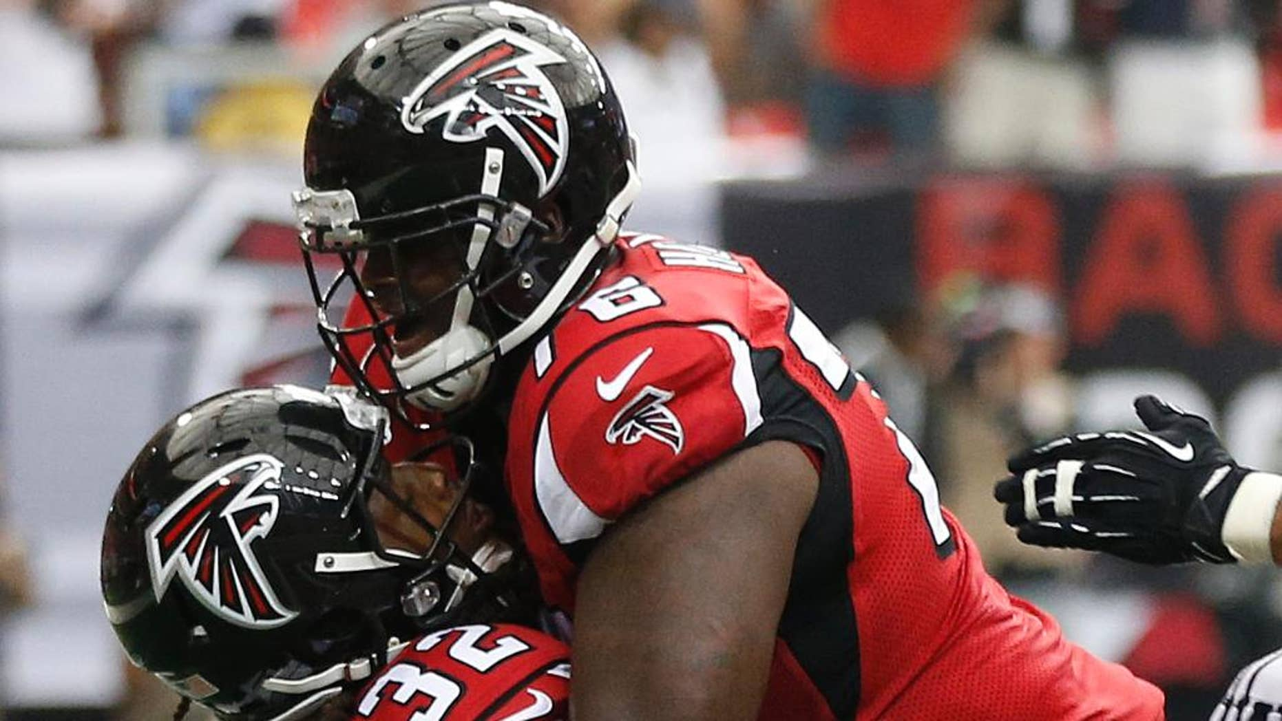 Atlanta Falcons tackle Lamar Holmes (76) embraces Atlanta Falcons running back Jacquizz Rodgers (32) after Rodgers scored a touchdown against the New Orleans Saints during the second half of an NFL football game, Sunday, Sept. 7, 2014, in Atlanta. (AP Photo/John Bazemore)