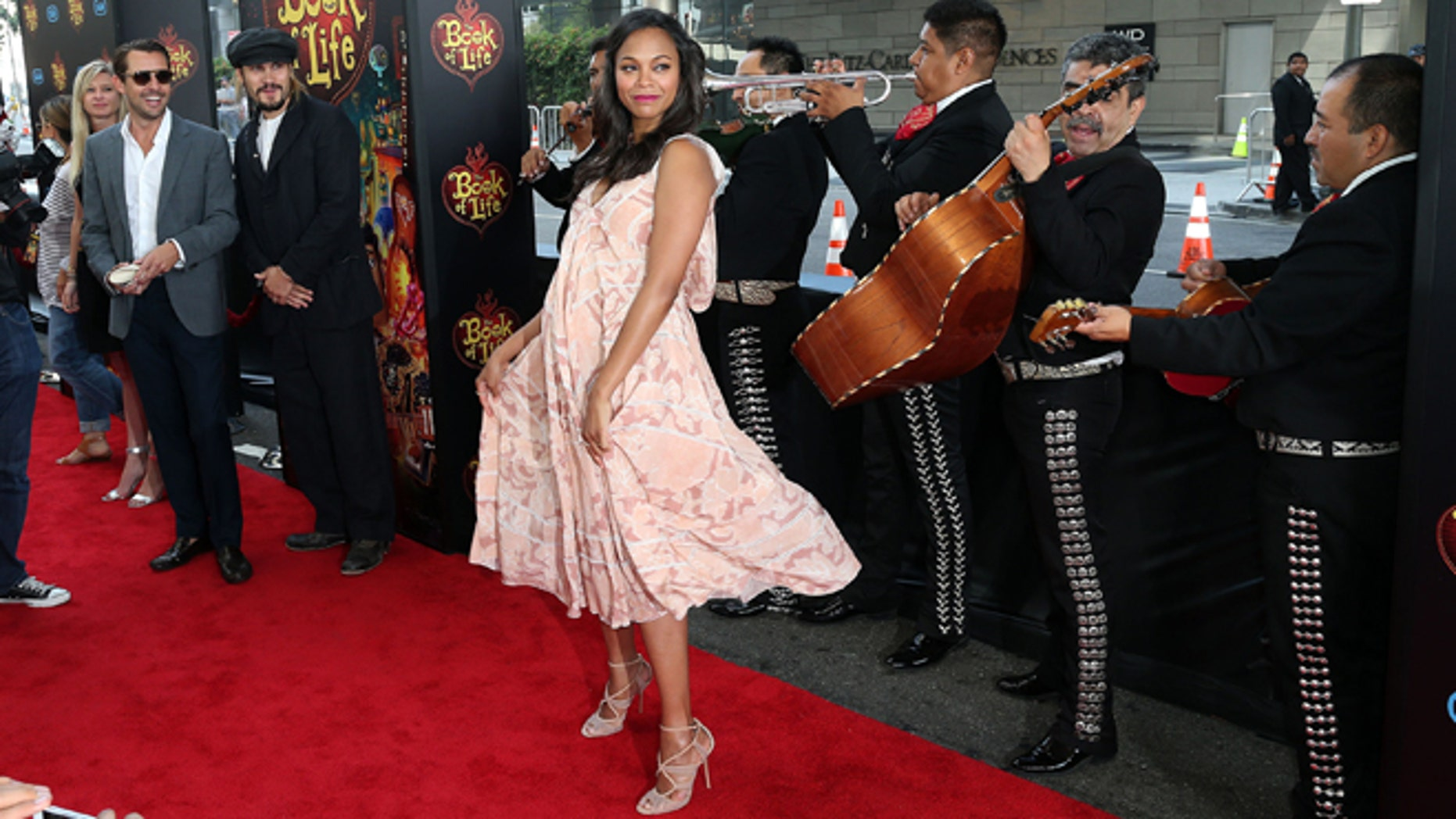"LOS ANGELES, CA - OCTOBER 12: Artist Marco Perego (L) watches his wife actress Zoe Saldana dance during the Premiere of Twentieth Century Fox and Reel FX Animation Studois' ""The Book of Life"" at the Regal Cinemas L.A. Live on October 12, 2014 in Los Angeles, California.  (Photo by Frederick M. Brown/Getty Images)"